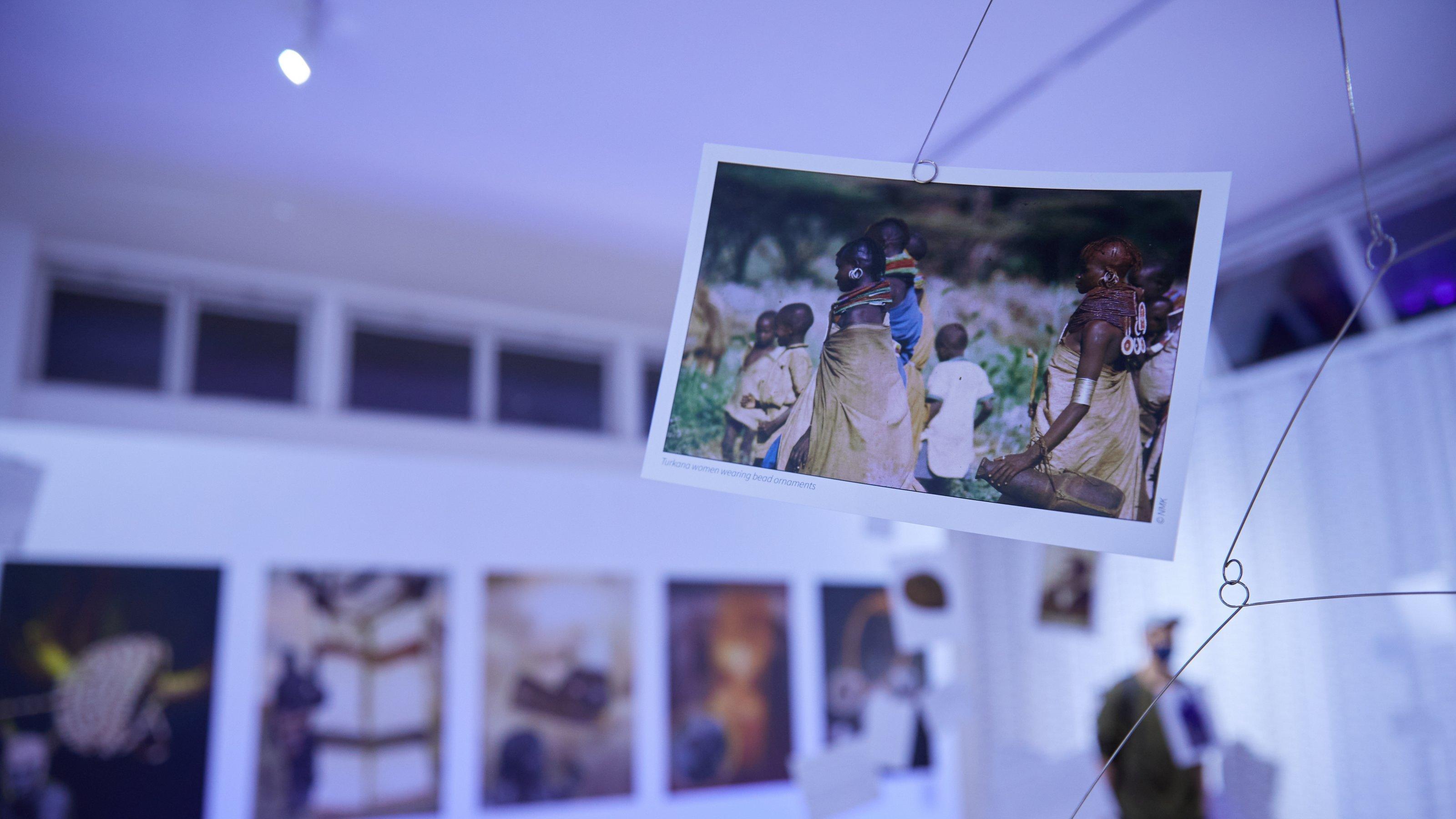 Im Mittelgrund hängt ein Foto an einer Art Mobile, darauf sind traditionell gekleidete Kenianerinnen und Kenianer zu sehen, die auffällige Schmuckstücke tragen. Im Hintergrund und verschwommen weitere Fotos.