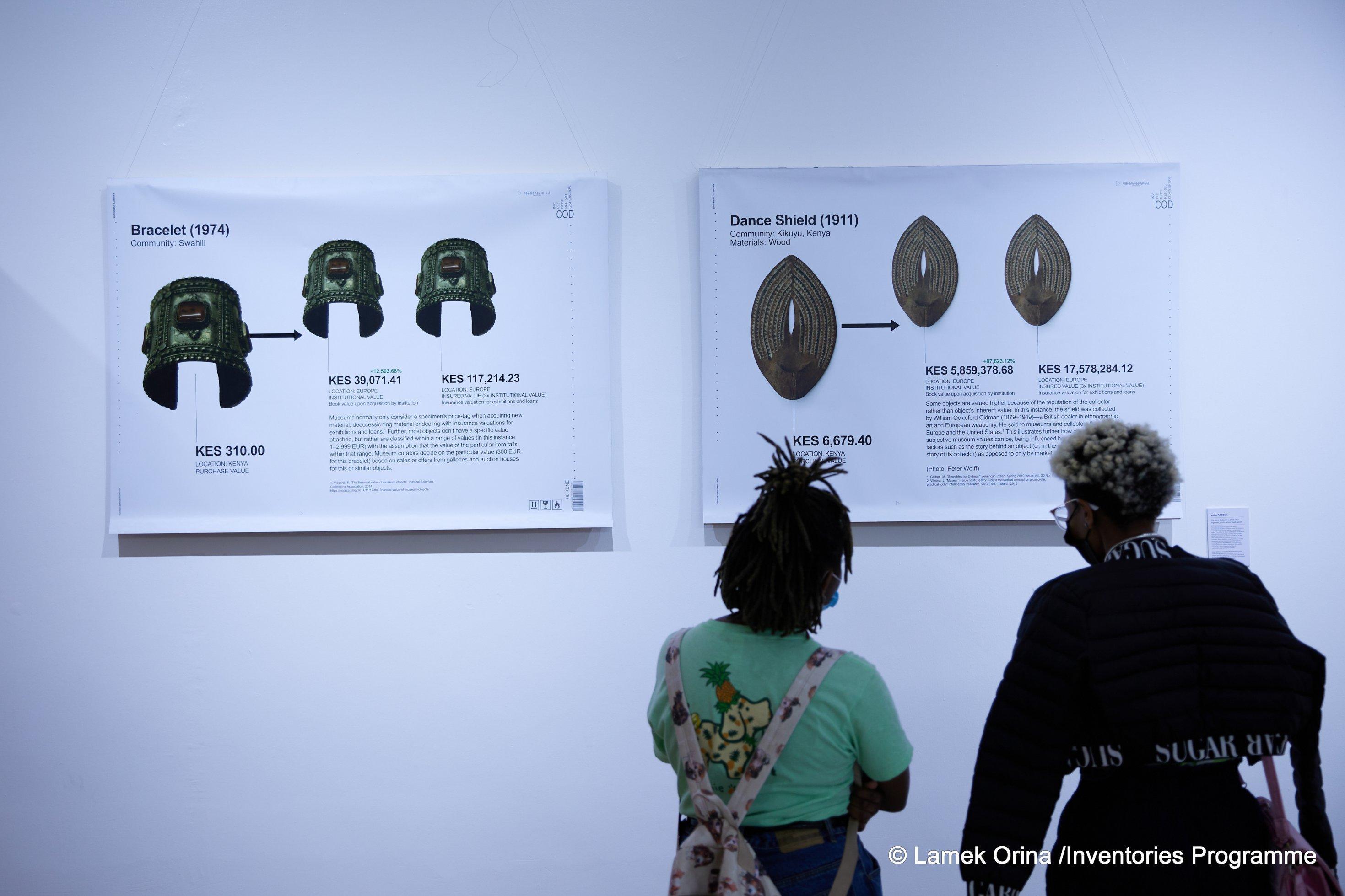 Zwei Frauen sind hinten zu sehen, sie betrachten in einer Ausstellung die großflächigen Abbildungen von offensichtlich afrikanischen Objekten.