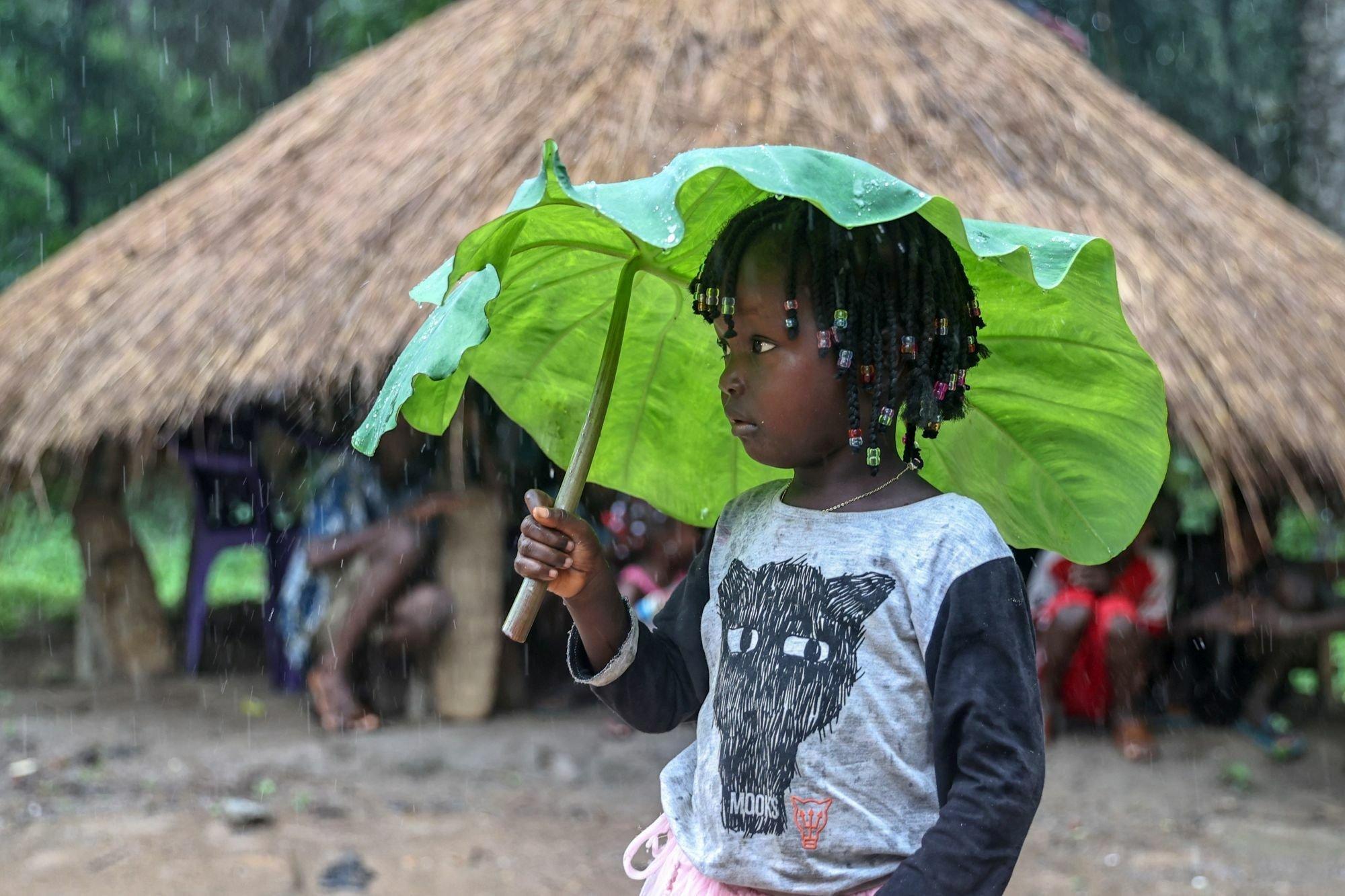 Ein Kind in Guinea im Regen benutzt ein Blatt als Regenschirm