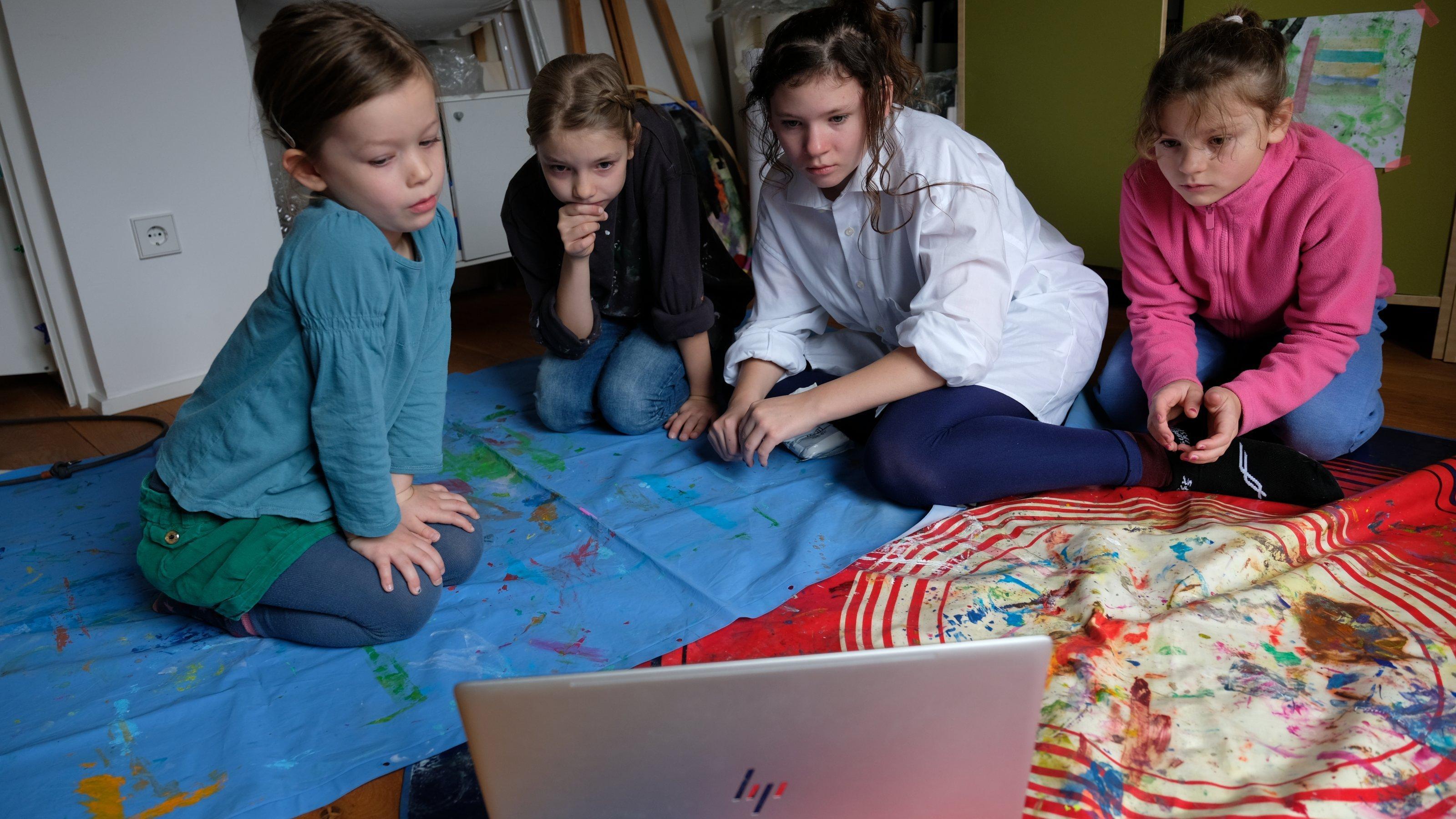 Vier Mädchen von fünf bis zwölf Jahren sitzen vor einem Notebook auf dem Boden und gucken im Internet ein Video. Die Kunstsammlung NRW erklärt auf YouTube für Kinder, wie einzelne Künstler gearbeitet haben.