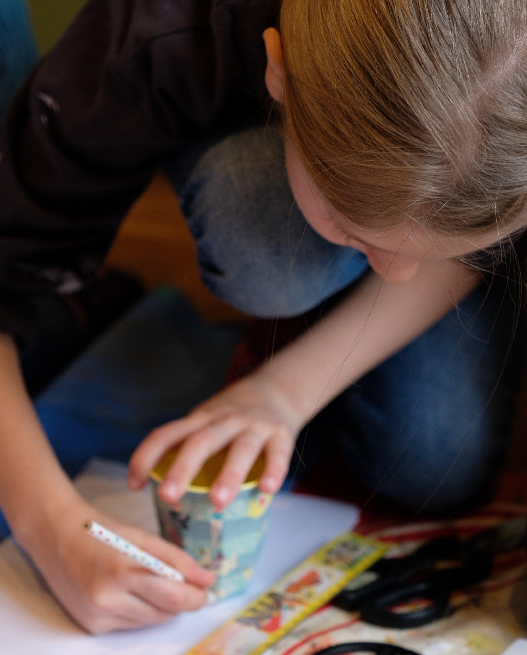 Tilda hockt auf dem Boden und hat einen Becher vor sich auf das Blatt Papier gestellt. Mit einem Stift fährt sie unten um den Becherboden herum – und hat eine runde Form gezeichnet.