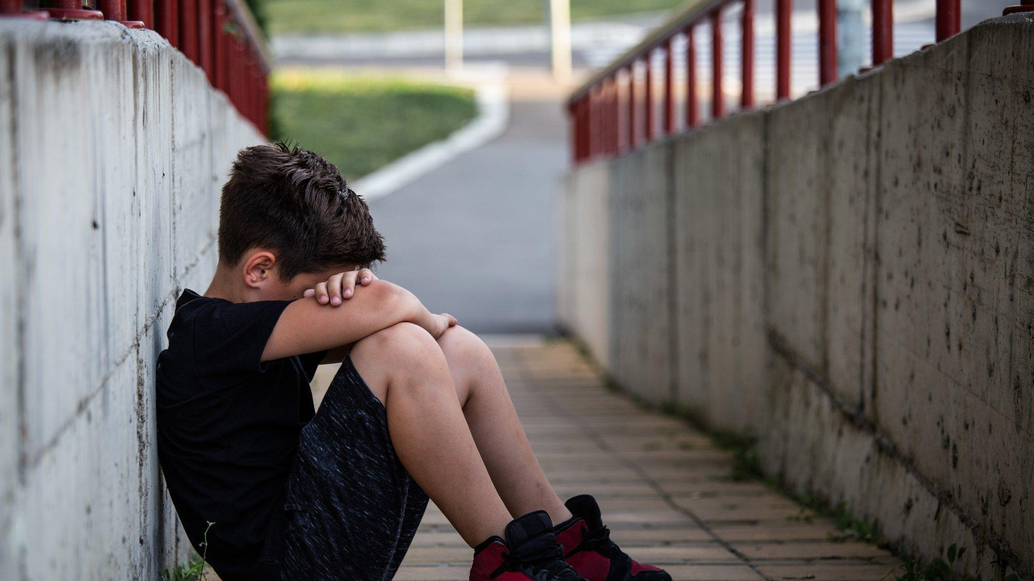 Symbolbild: Kleiner Junge sitzt traurig auf der Straße