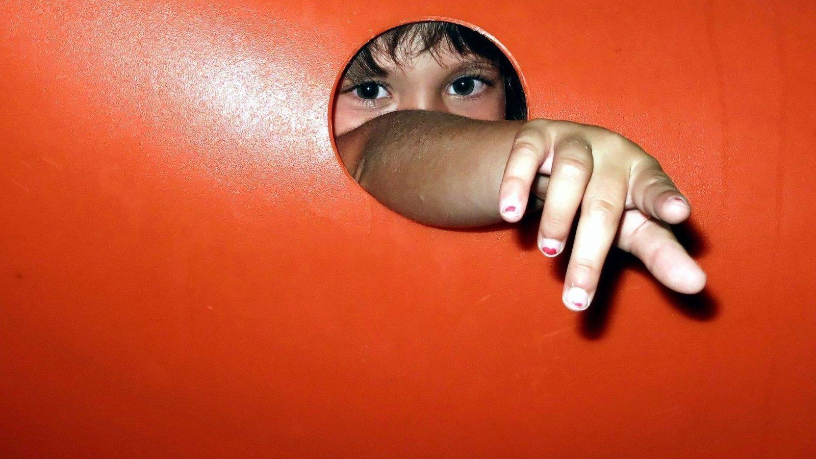 Eine Kinderhand fasst durch ein Loch
