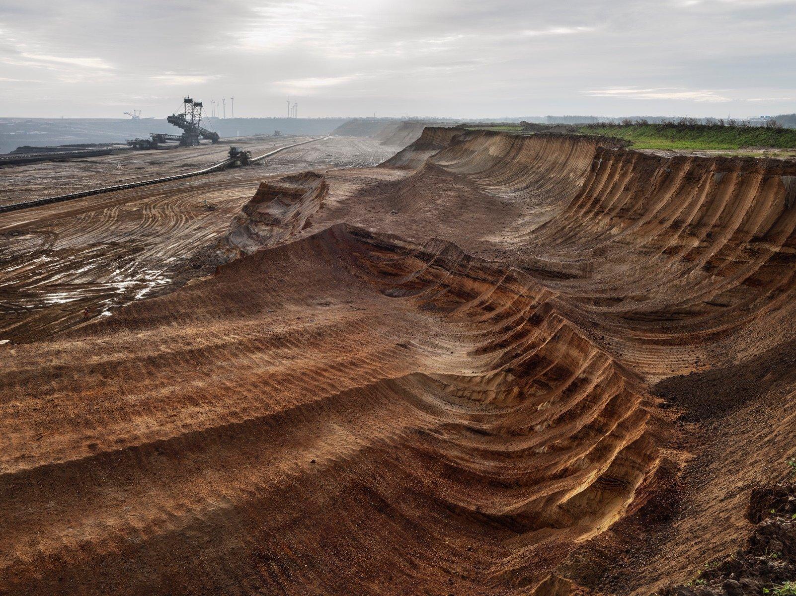 Das Bild zeigt die Braunkohltagebau-Grube von Garzweiler in Nordrhein-Westfalen, eine weite ausgeräumte Sandlandschaft mit einem Kohlebagger am Horizont.