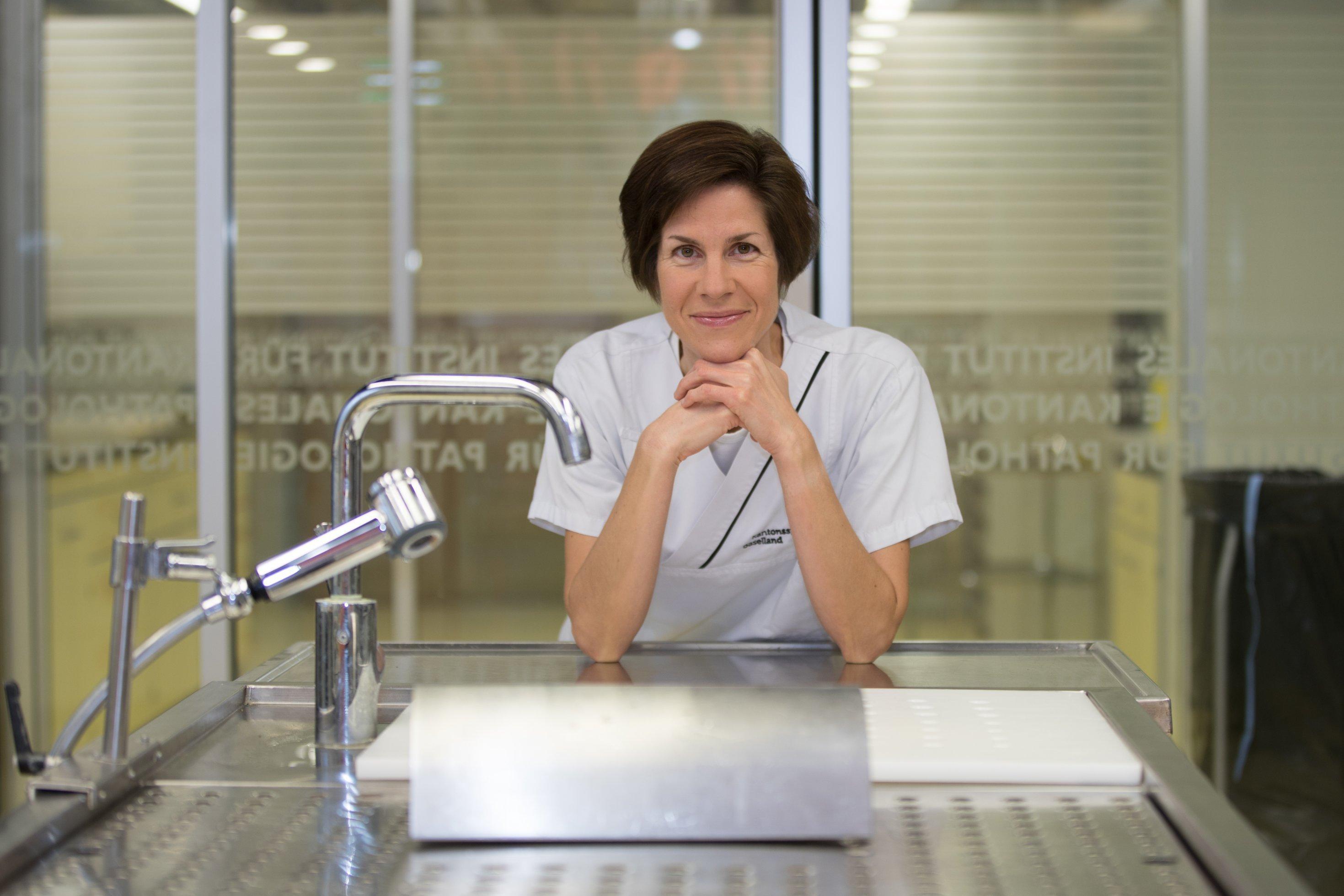 Eine Frau, die Pathologin Kirsten Mertz, steht abgestützt an einem Obduktionstisch in einem Obduktionssaal.