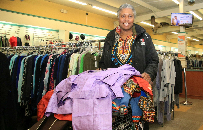 Eine Frau Anfang 60schiebt einen prallgefüllten Einkaufswagen durch ein Warenhaus.