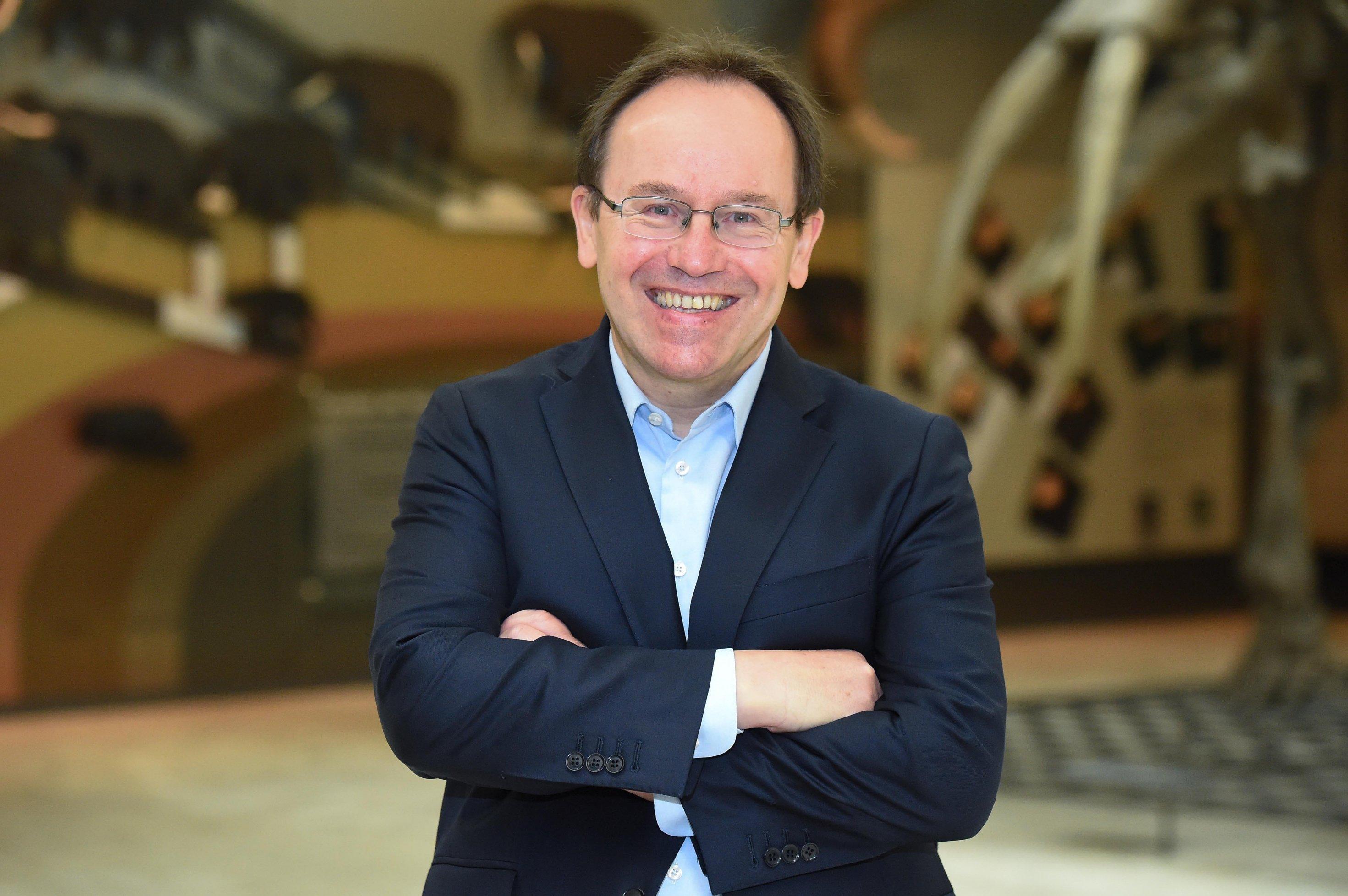 Der Wissenschaftler mit Brille und dunkelblauem Sakko lächelt