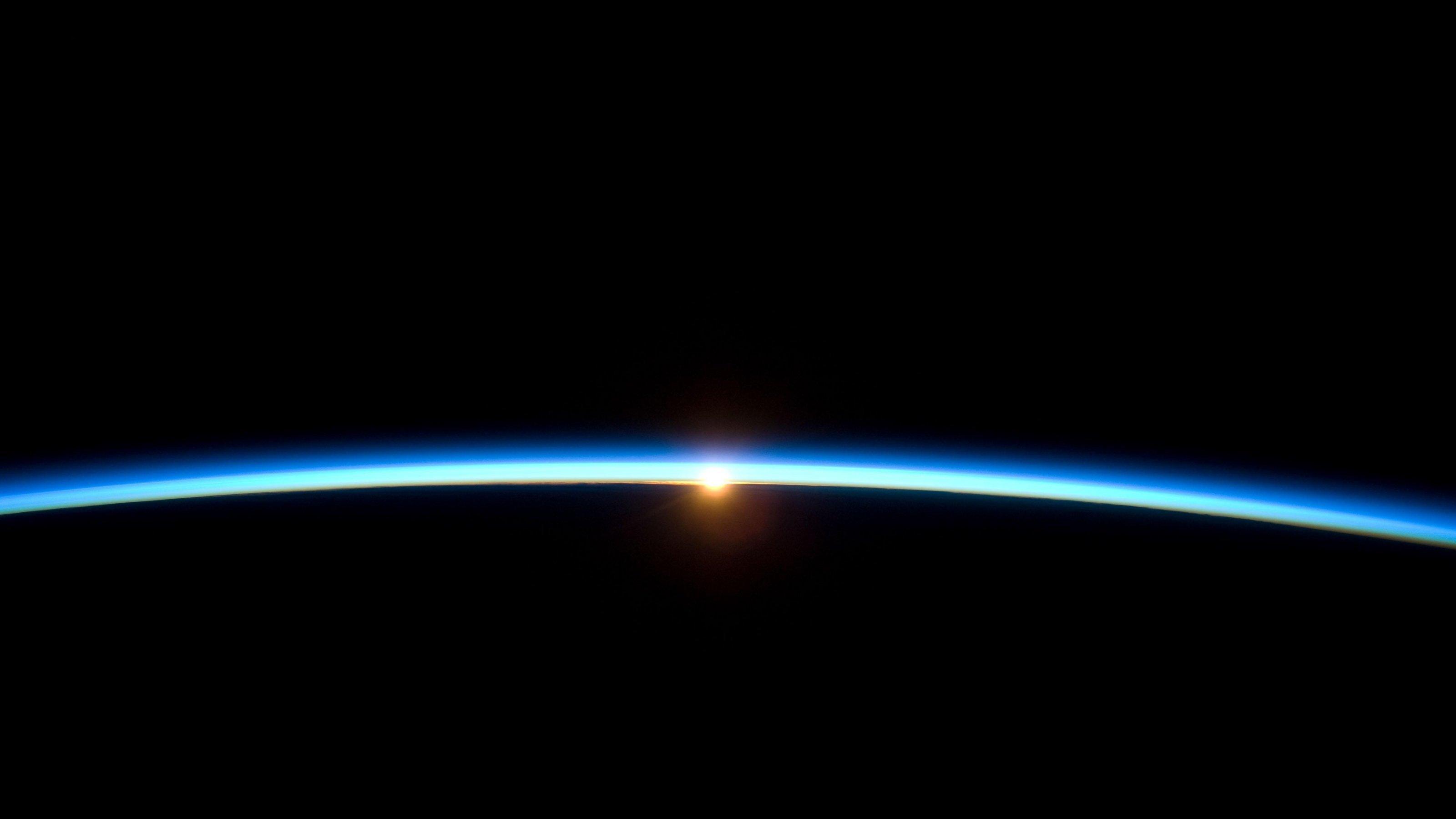 Aufnahme des Sonnenaufgangs aus großer Höhe. Ein heller Streifen schiebt sich über den ründlichen Horizont.