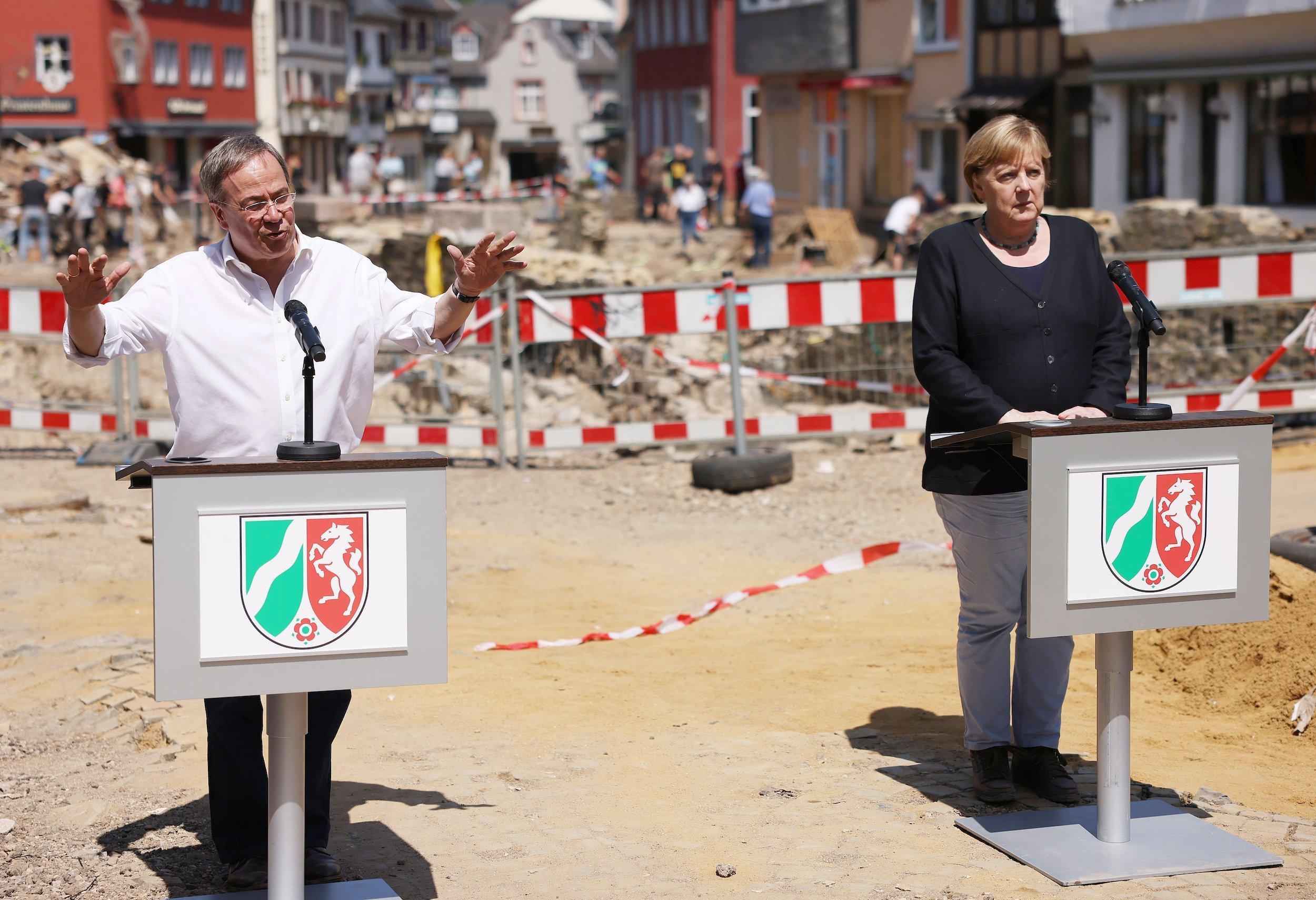 Armin Laschet (CDU), Ministerpräsident von Nordrhein-Westfalen, und Bundeskanzlerin Angela Merkel (CDU) geben eine Pressekonferenz in Bad Münstereifel vor Trümmern.