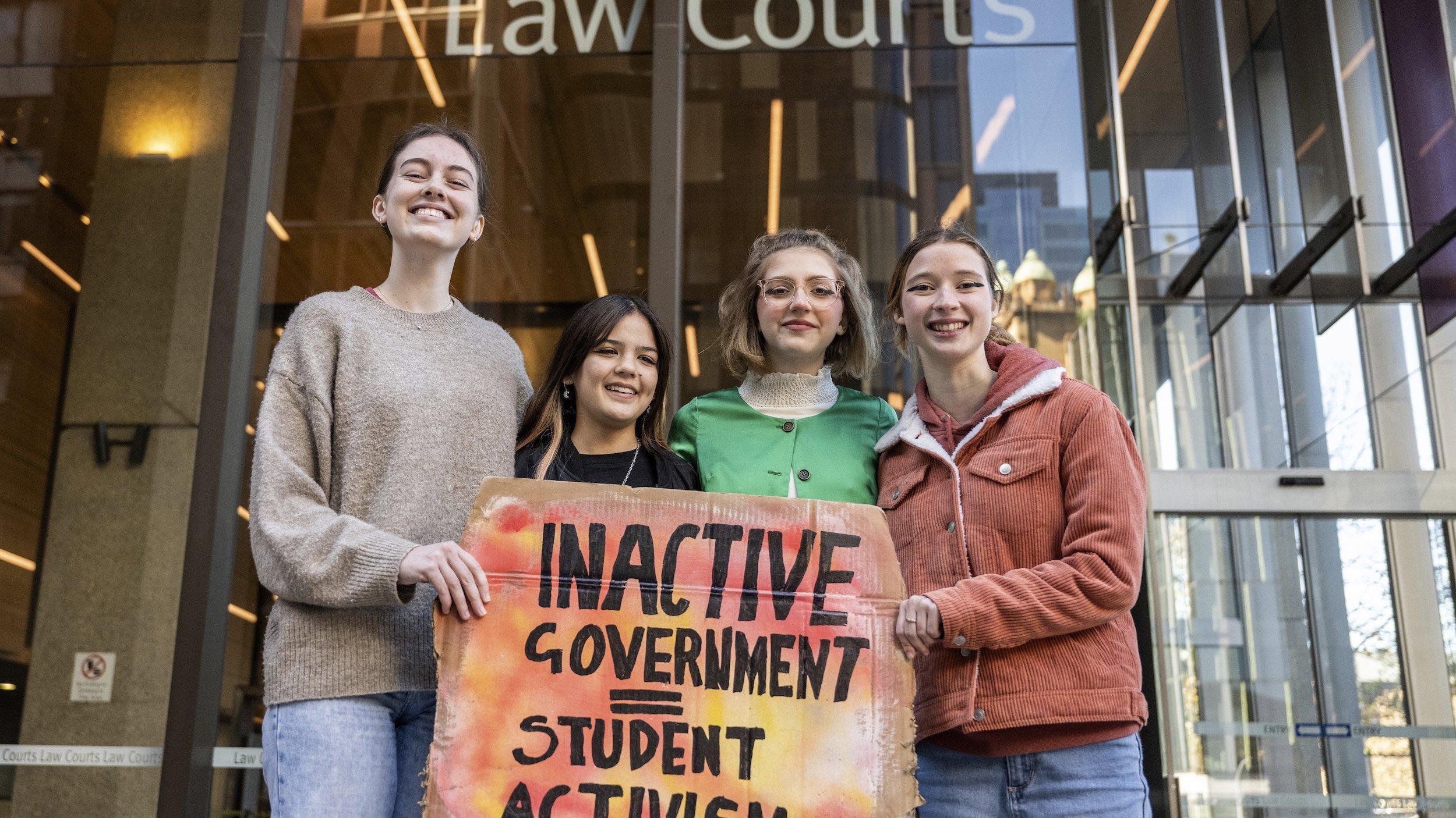Die vier jugendlichen Klägerinnen vor dem Gericht mit einem Schild auf dem steht: Inaktive Regierung, aktivistische Studentinnen.