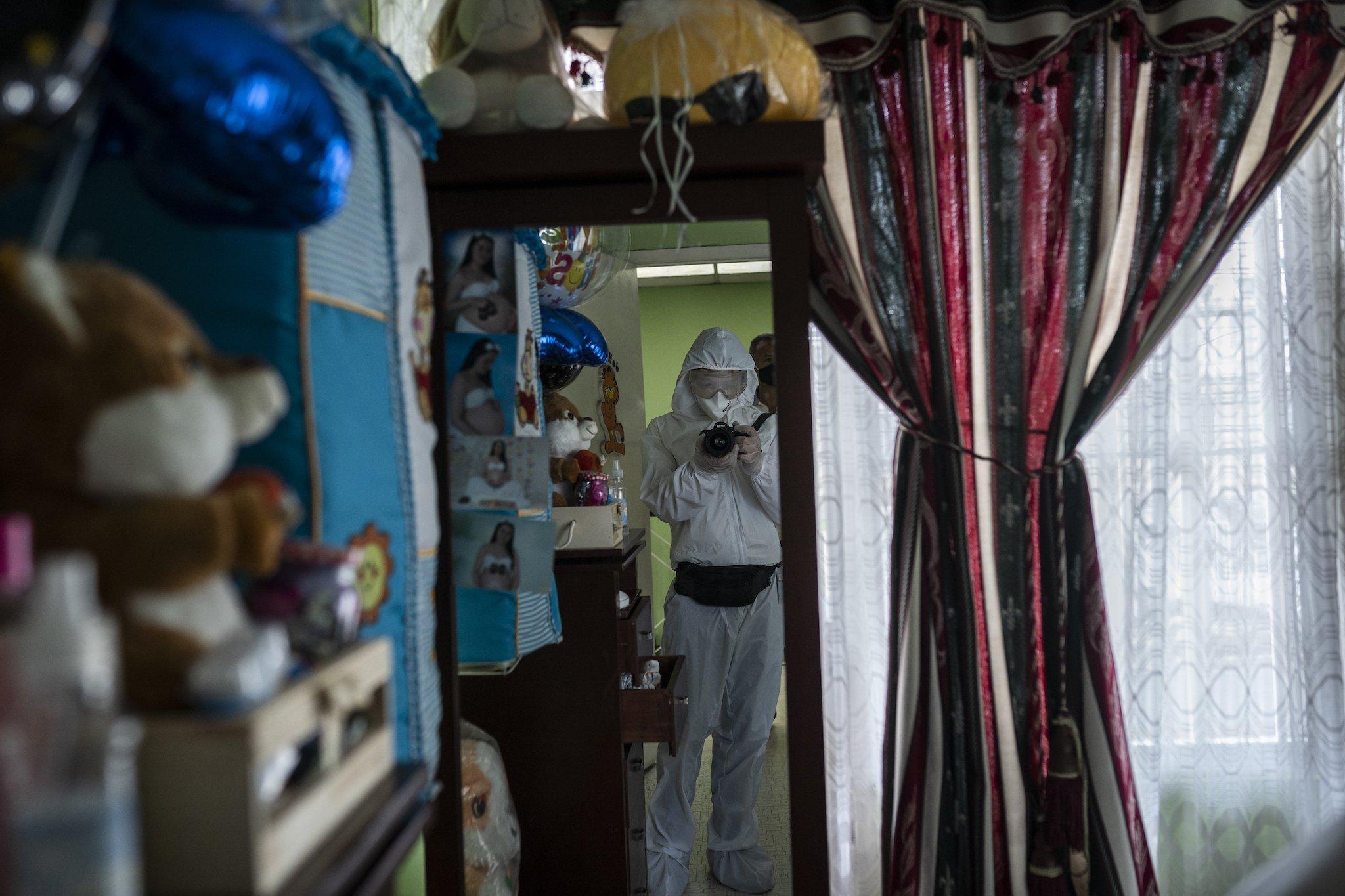 Der Fotograf trägt Ganzkörperanzug mit Kapuze, Mundschutz, Brille, Füßlinge und Handschuhe.