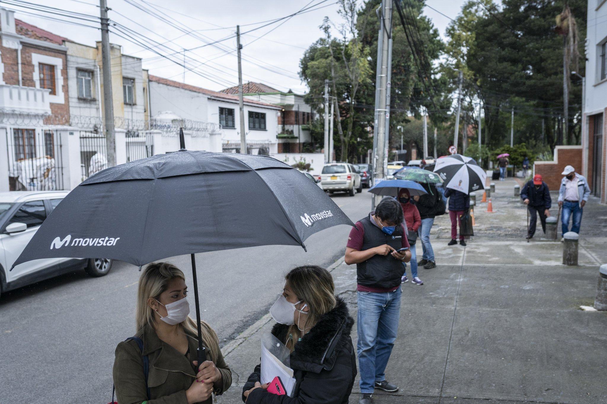 Die Menschen halten Abstand, tragen Mundschutz und Regenschirme, weil es zu regnen begann.