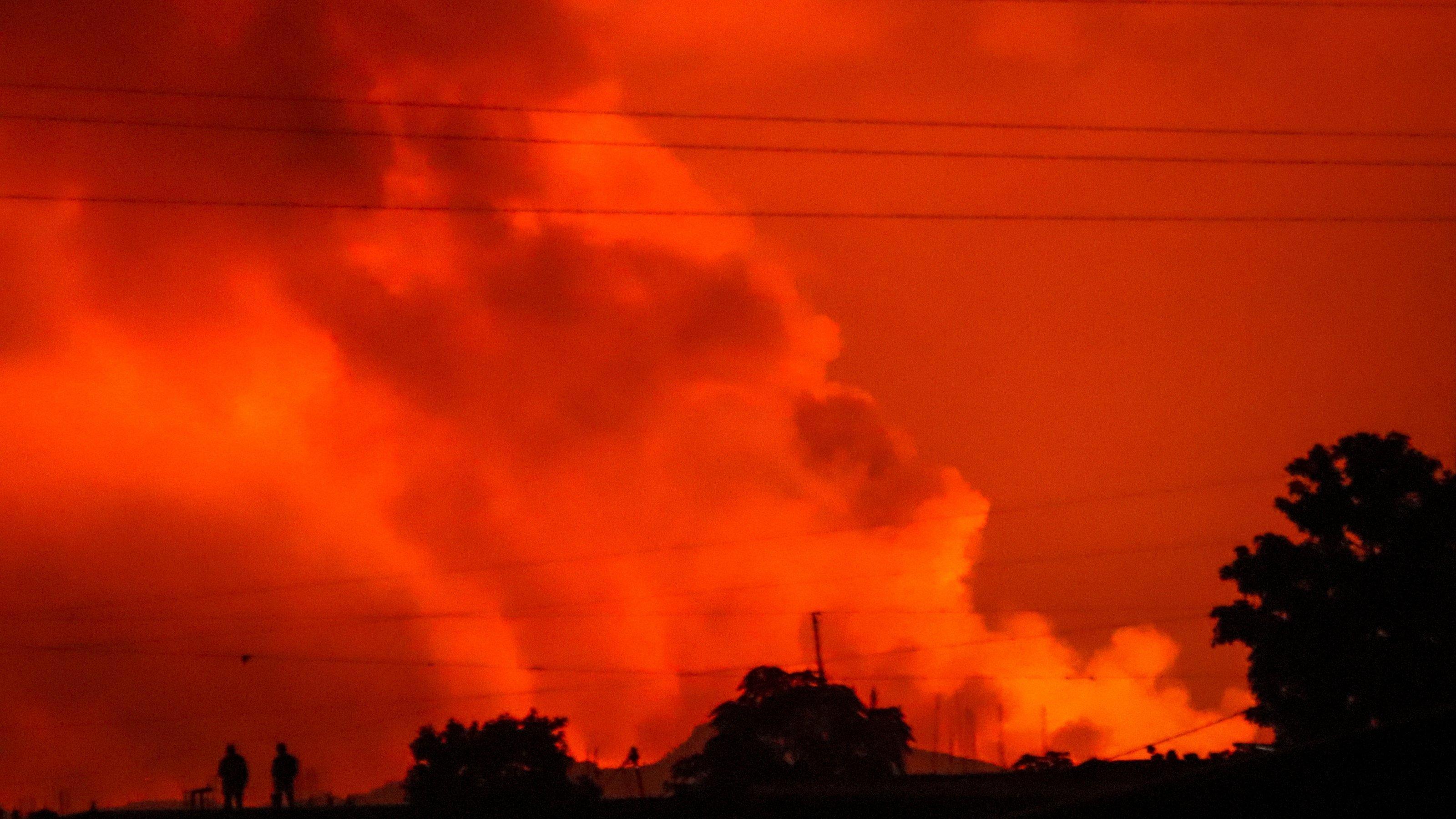 Zwei Menschen zeichnen sich als Silhouetten vor dem Nachthimmel ab, der durch den Ausbruch des Vulkans Nyiragongo am 22. Mai 2021rot gefärbt ist.