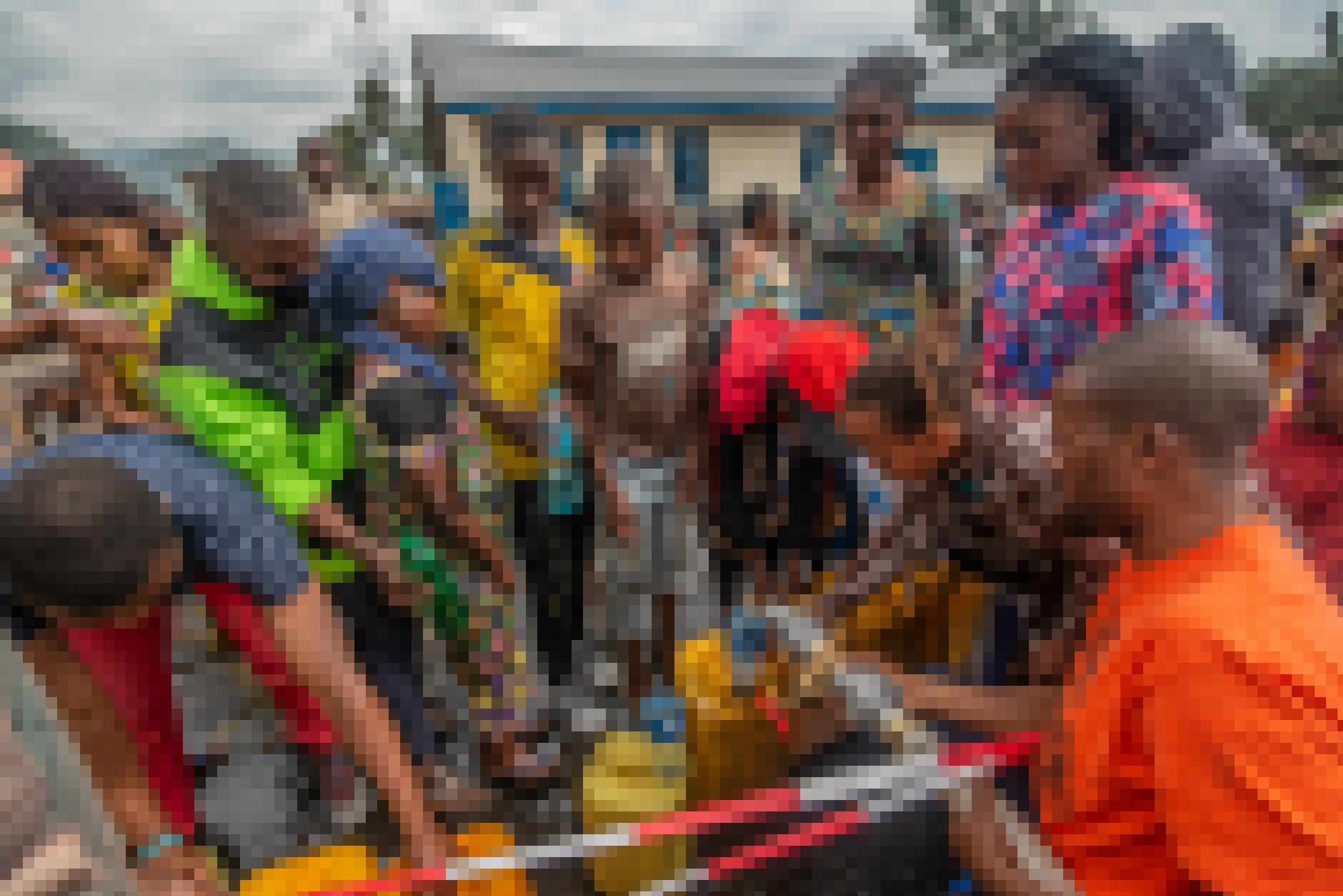 Menschen stehen Schlange für Trinkwasser, das sie dann in gelben 20-Liter-Plastikkanistern mitnehmen.