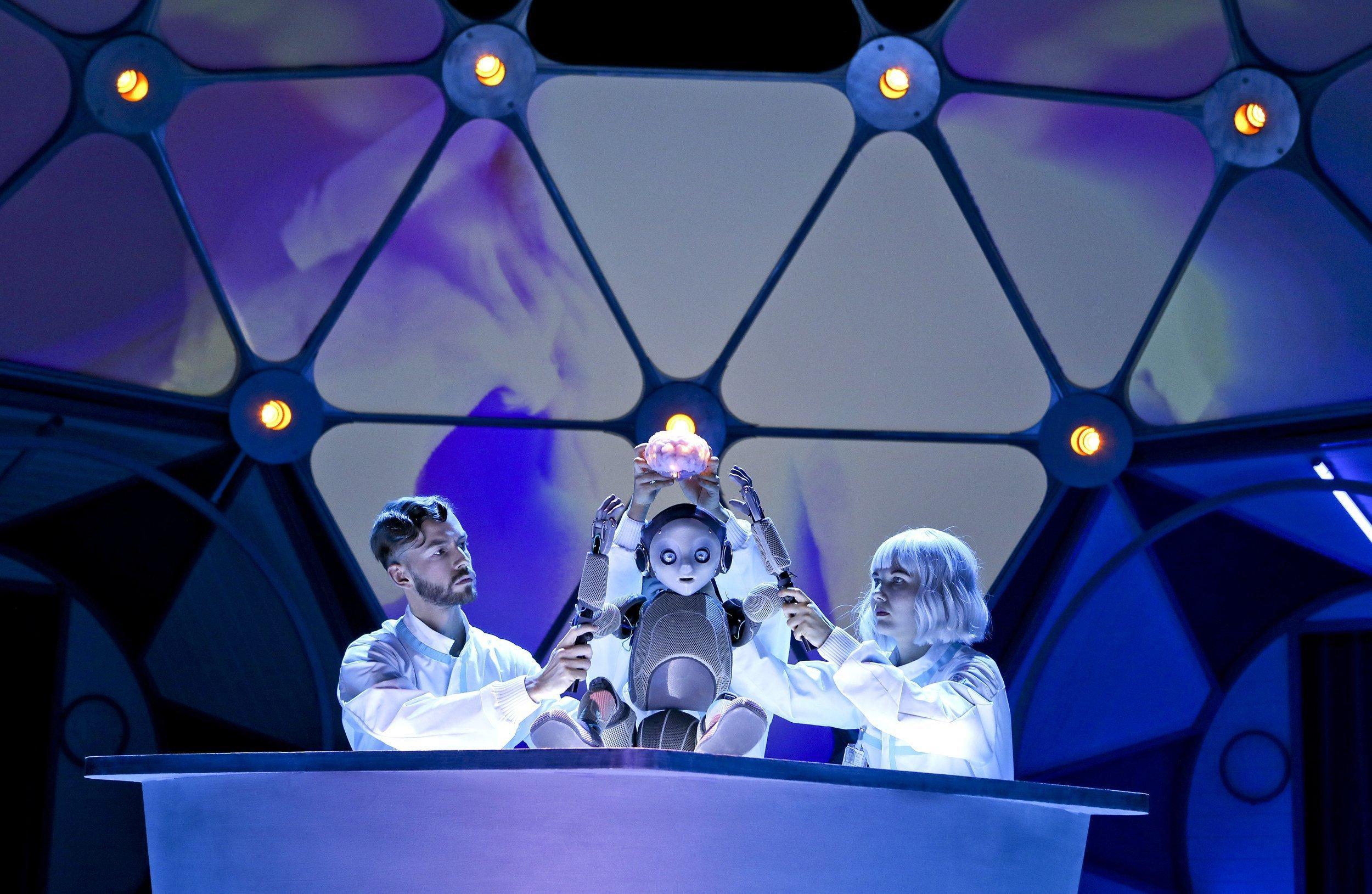 Die Schauspieler Franziska und Markus spielen zwei Forscher. Als Forscher bauen sie ein künstliches Gehirn und geben es einem Roboterjungen. Sie spielen das als Theaterstück auf der Bühne.
