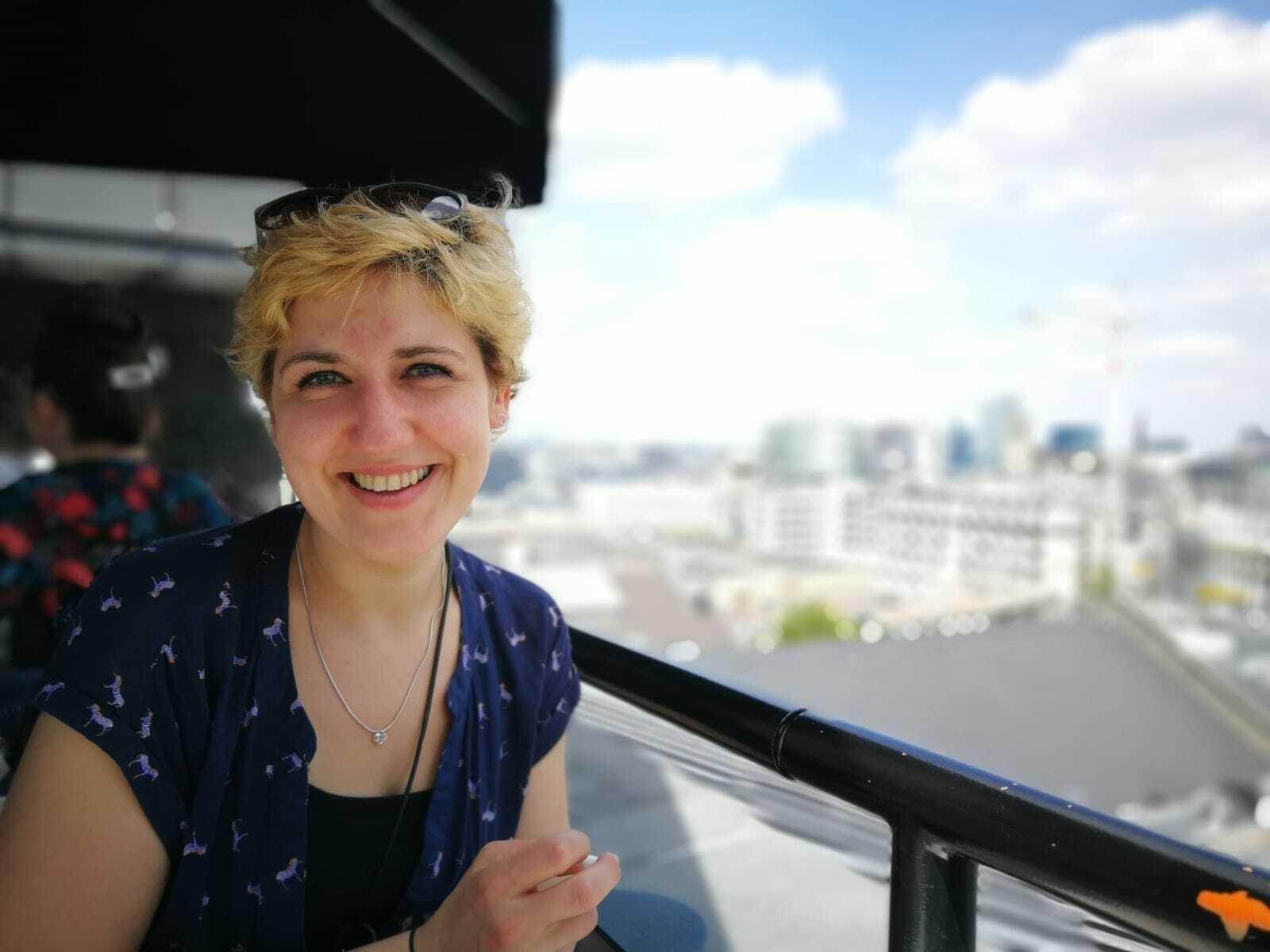 Hannah Brüggemann bei sommerlichem Wetter mit kurzärmeliger, dunkelblauer Bluse und blonden Haaren vor einem weiten Horizont.