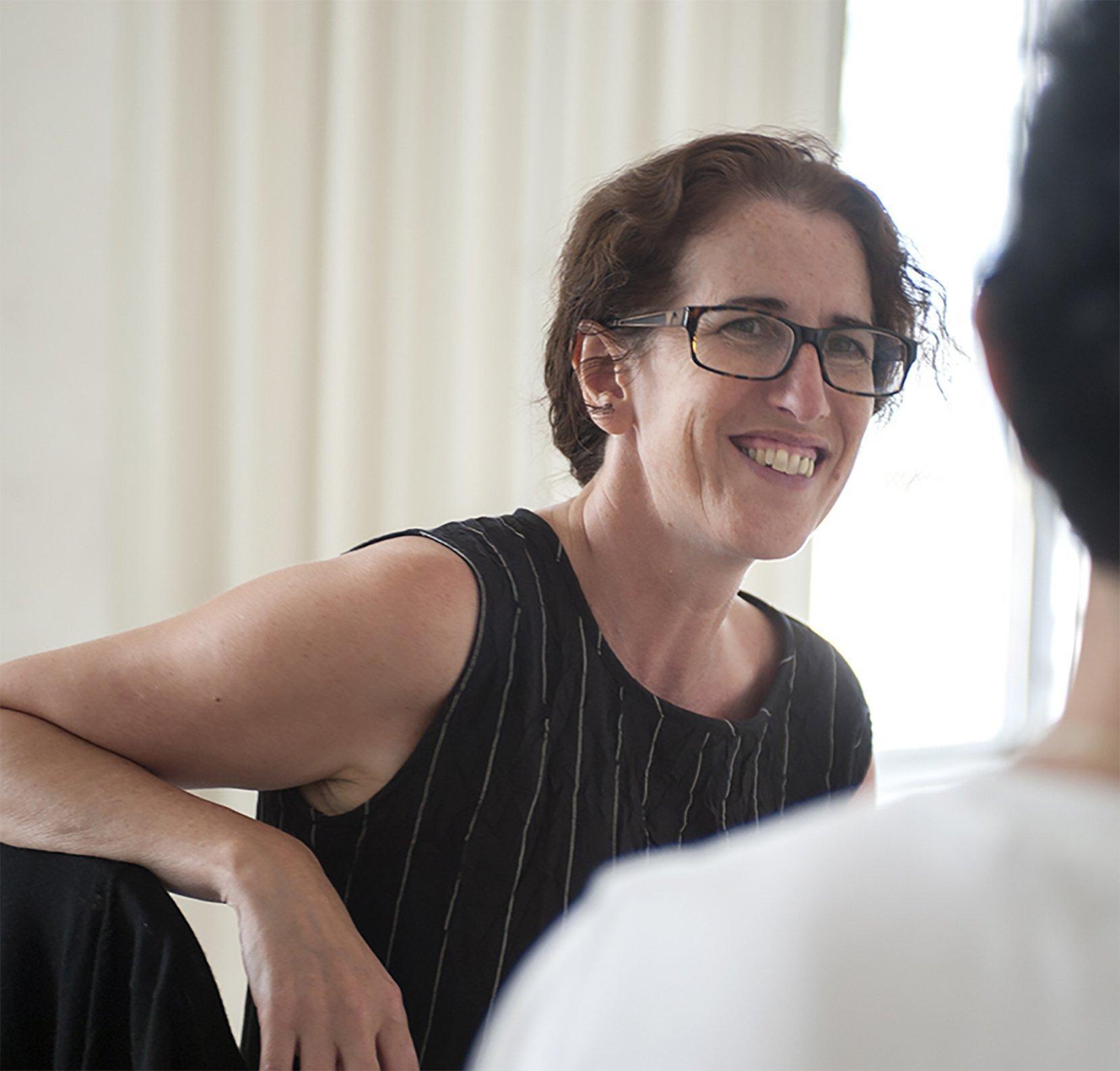 Sue Buckmaster trägt auf dem Foto kurze, dunkelbraune Haare und eine schwarze Brille. Sie ist gerade mit jemandem im Gespräch, von dem man nur einen kleinen Teil des Rückens sieht.