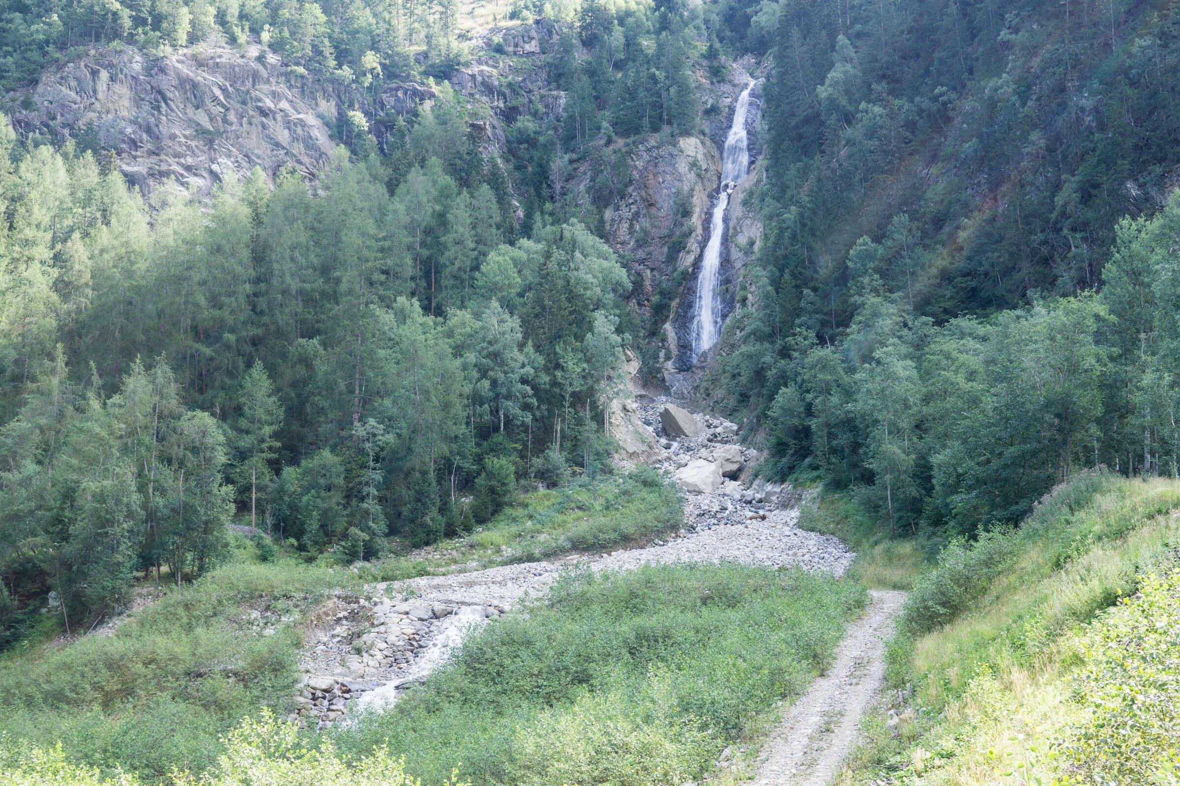 Felswand mit schmalem Wasserfall in Gebirgslandschaft