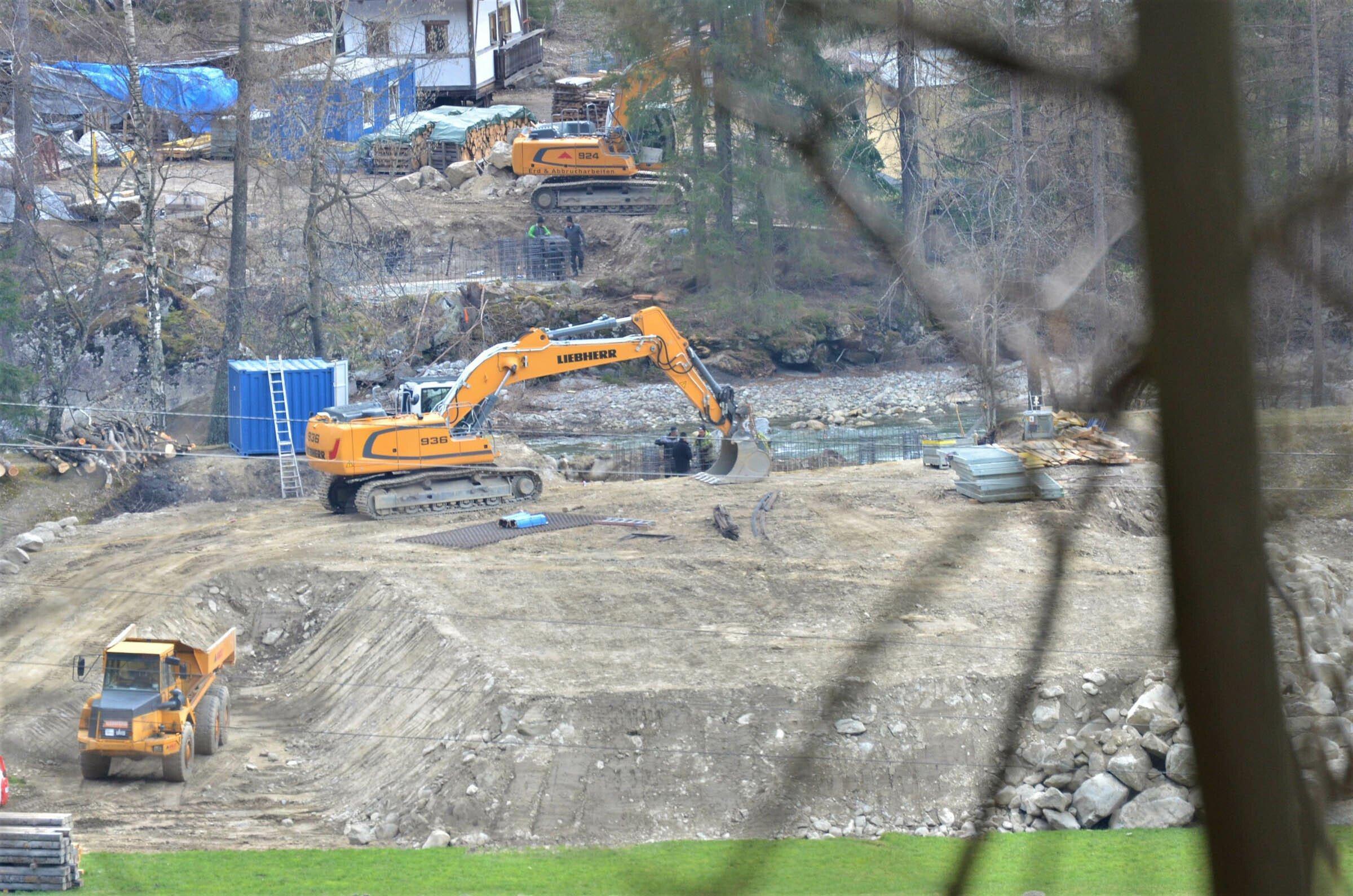 Blick hinunter auf einen Bach und Baufahrzeuge, die am Ufer den Boden aufgraben.