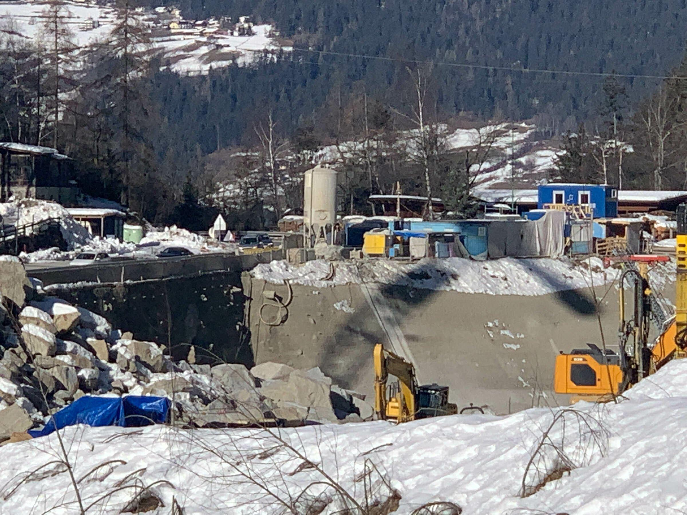 Baustelle an Gebirgsbach mit Betonwand und Baustellengerätschaften