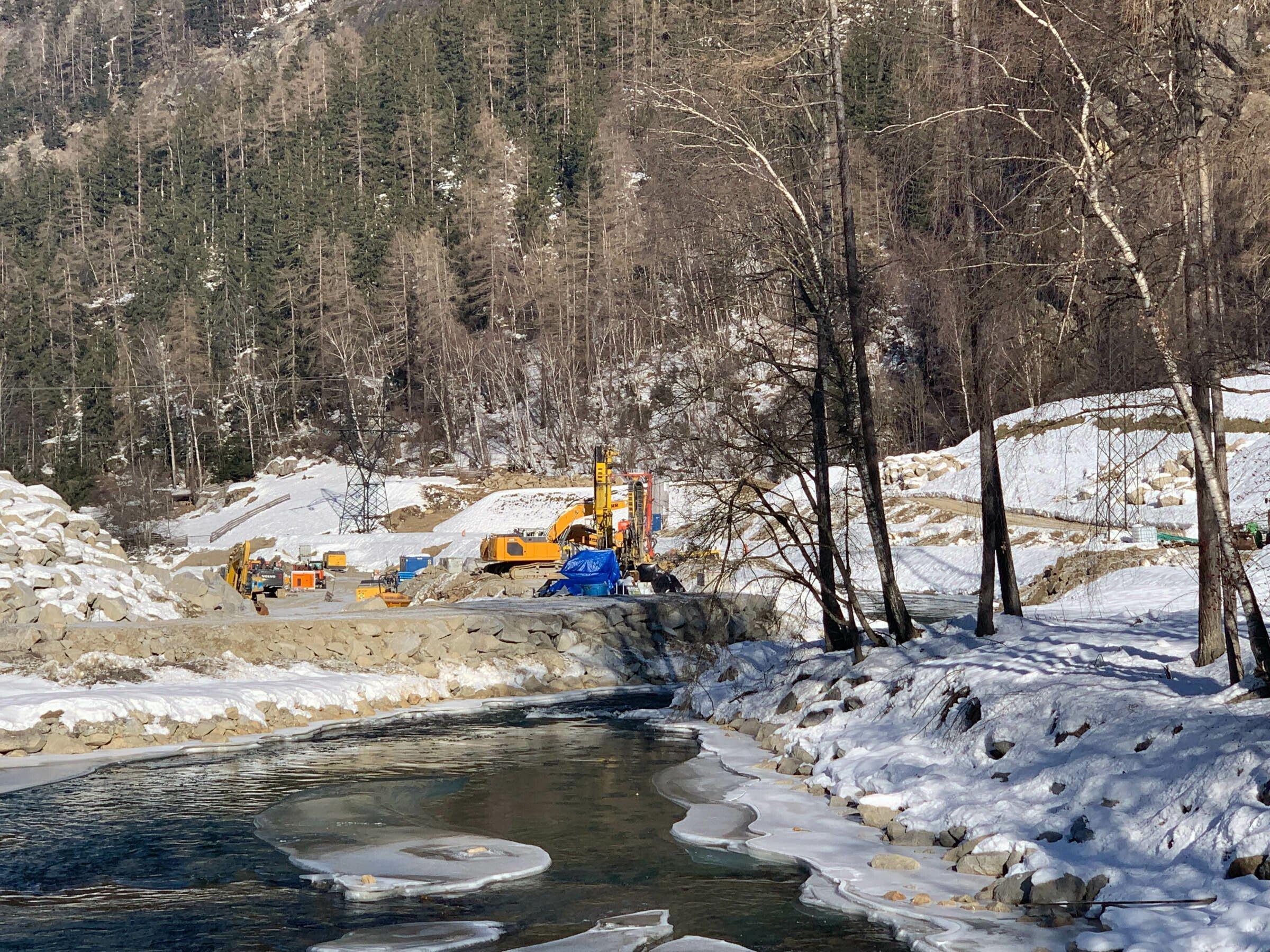 Gebirgsbach mit Eis und Schnee, am Ufer wenige Bäume, im Hintergrund Bagger und eine Baustelle