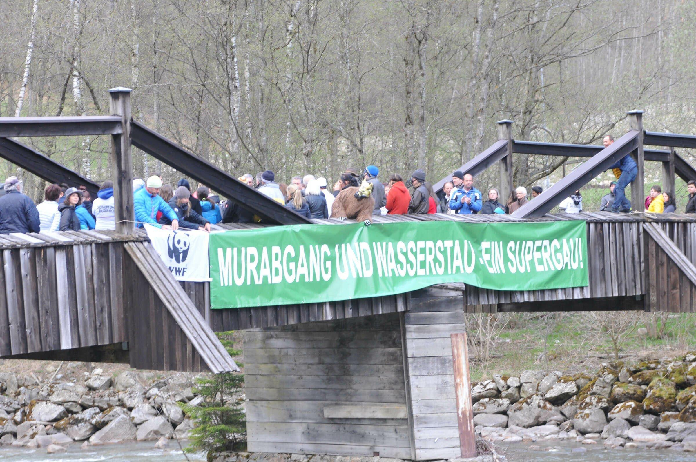 Demonstranten auf alter Holzbrücke, auf der ein grünes Transparent hängt mit dem Text: Murabgang und Wasserstand – ein Supergau!