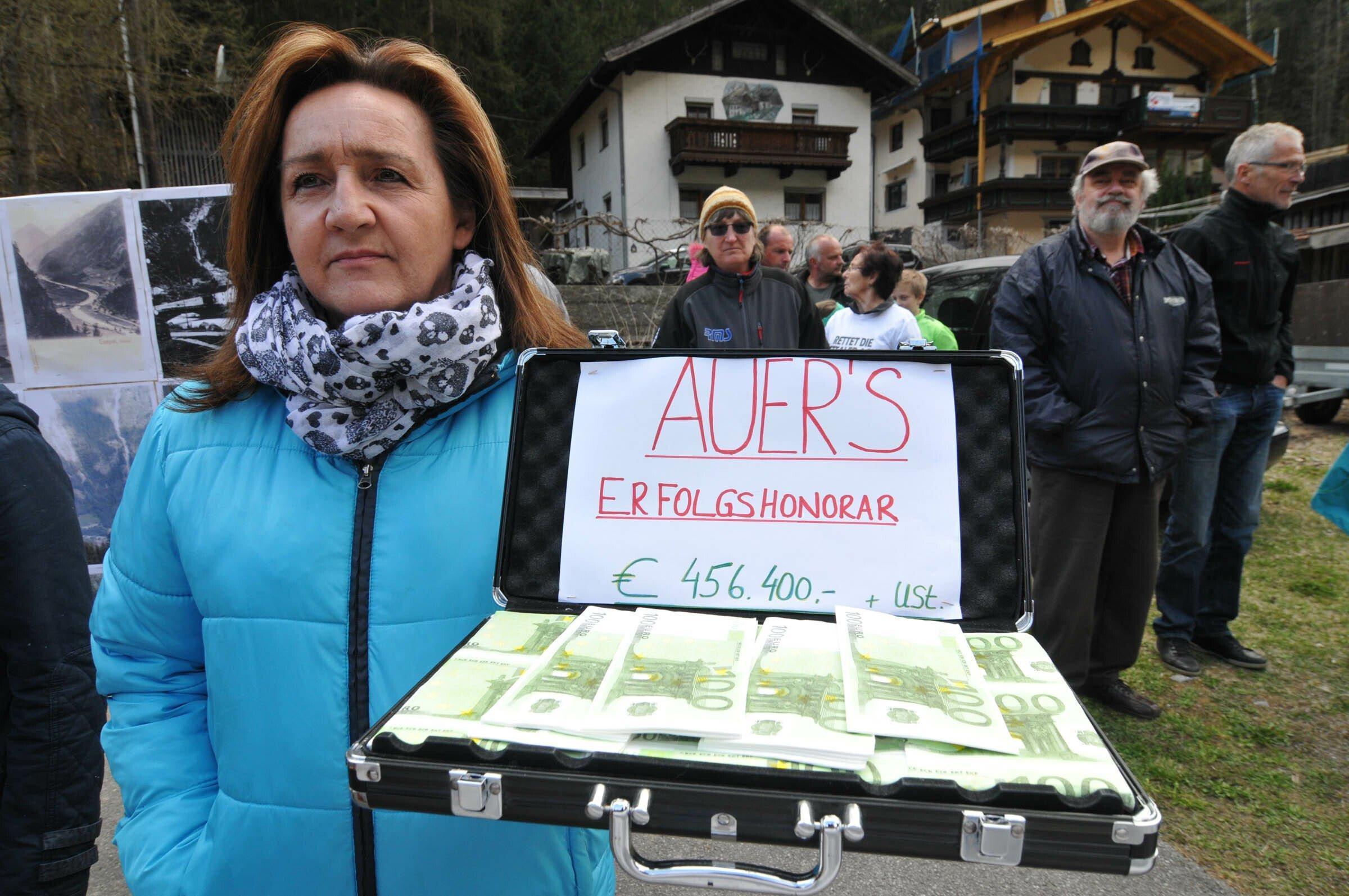 Frau mit Aktenkoffer mit Papiergel. Auf einem Zettel steht: Auers Erfolgshonorar € 456.400 + USt.