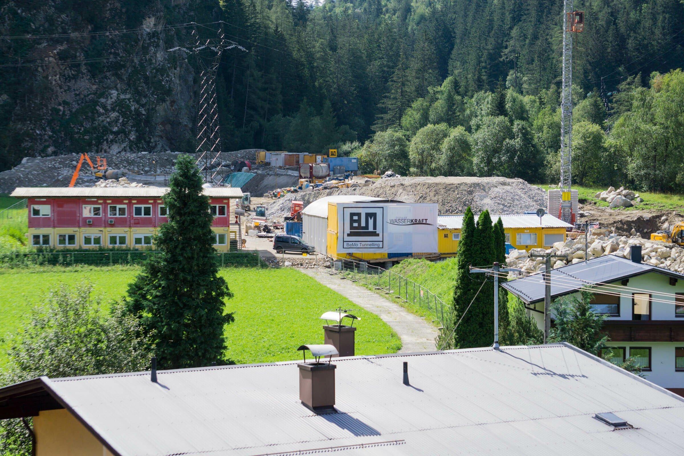Baustelle auf einer Wiese neben Einfamilienhäusern