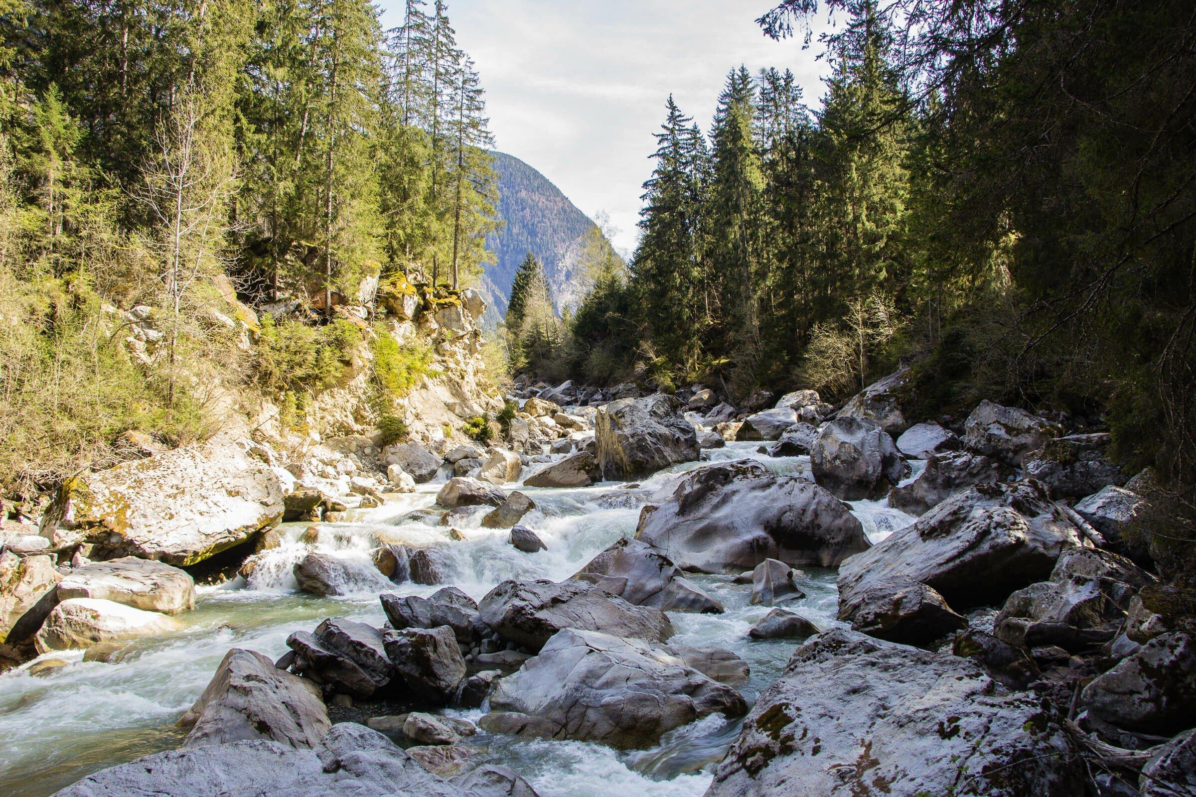 Gletscherbach mit großen Steinen und wildem Wasser.