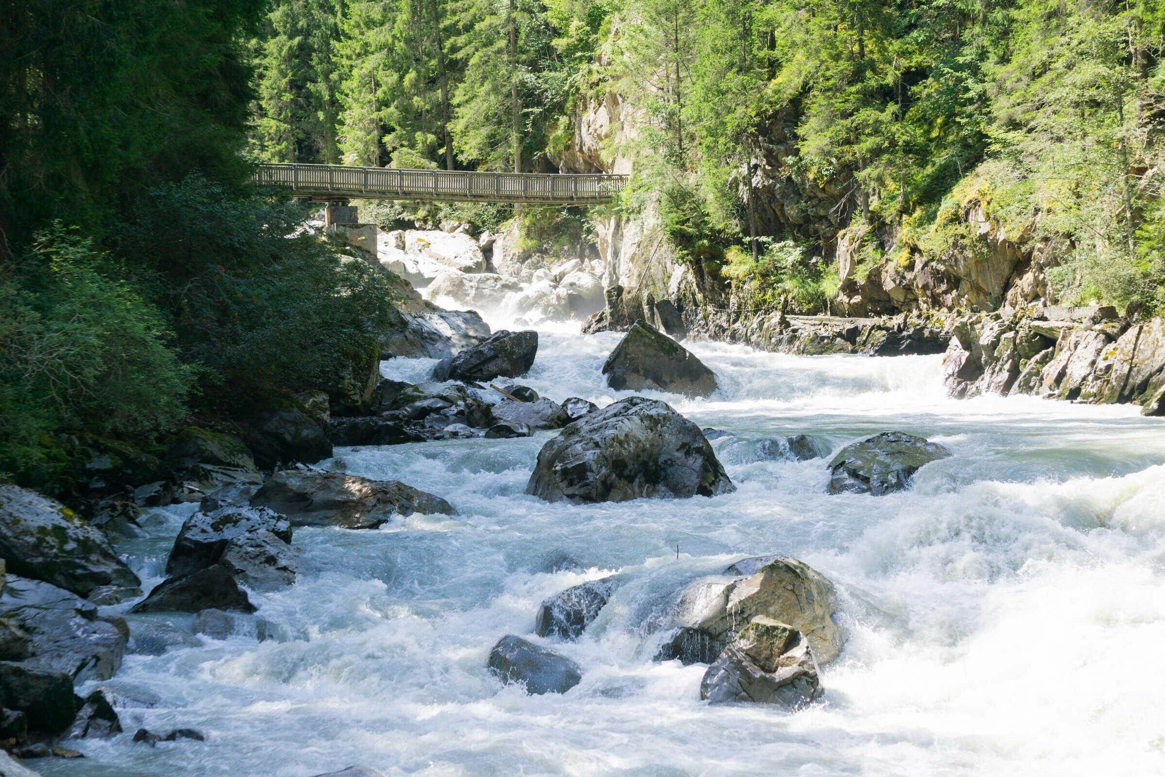 Gletscherbach im Wald mit Felsen und weiß schäumendem Wasser, im Hintergrund eine schmale Holzbrücke.