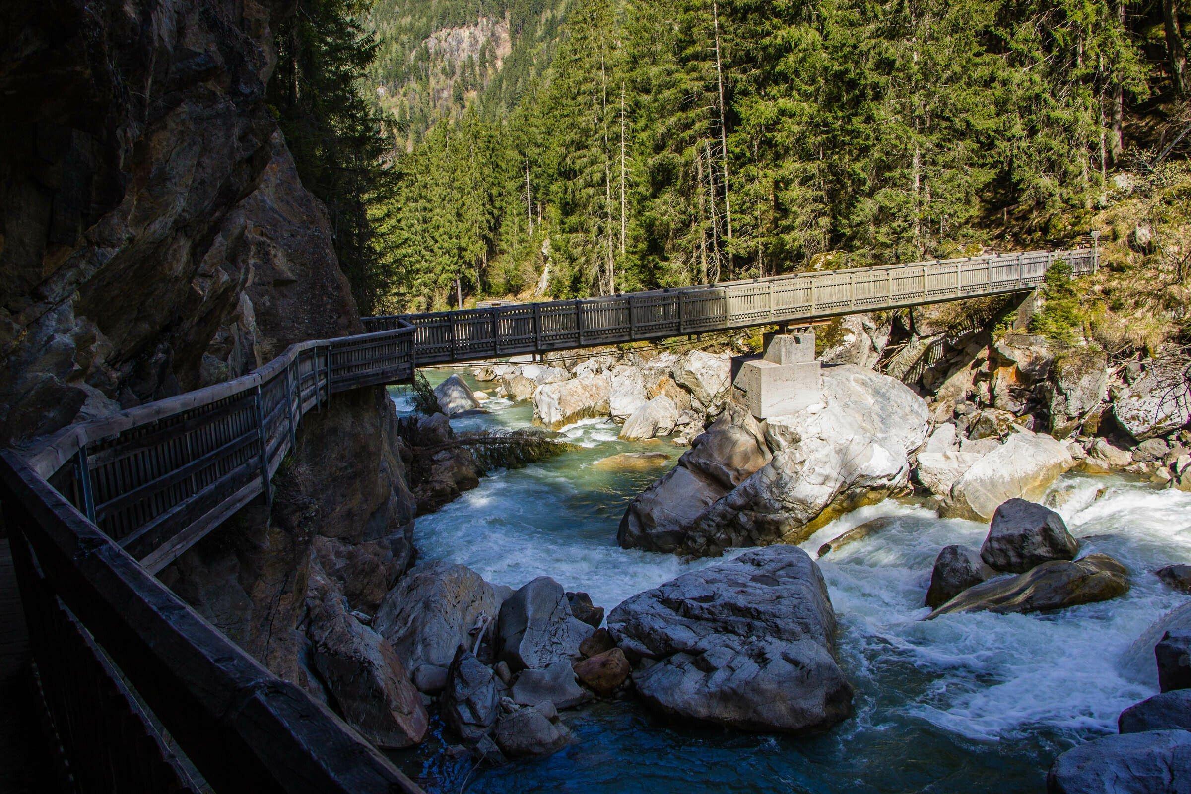 Wilder Gletscherbach mit großen Steinen und einer querenden Holzbrücke.