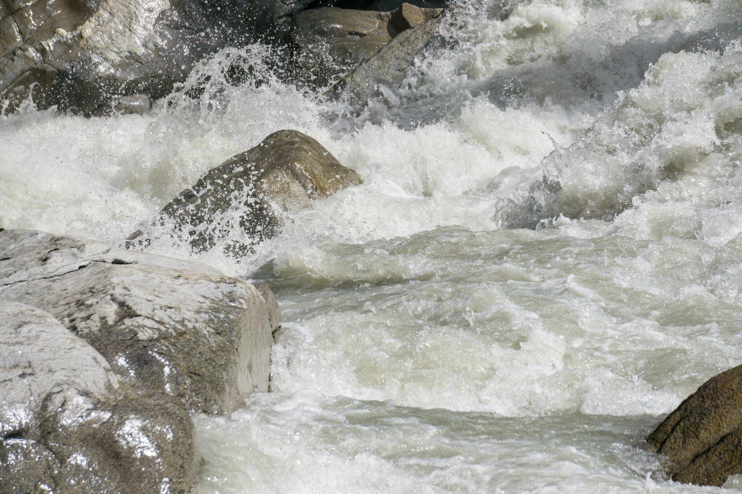 Felsblöcke im Fluss mit wild schäumendem weißen Wasser