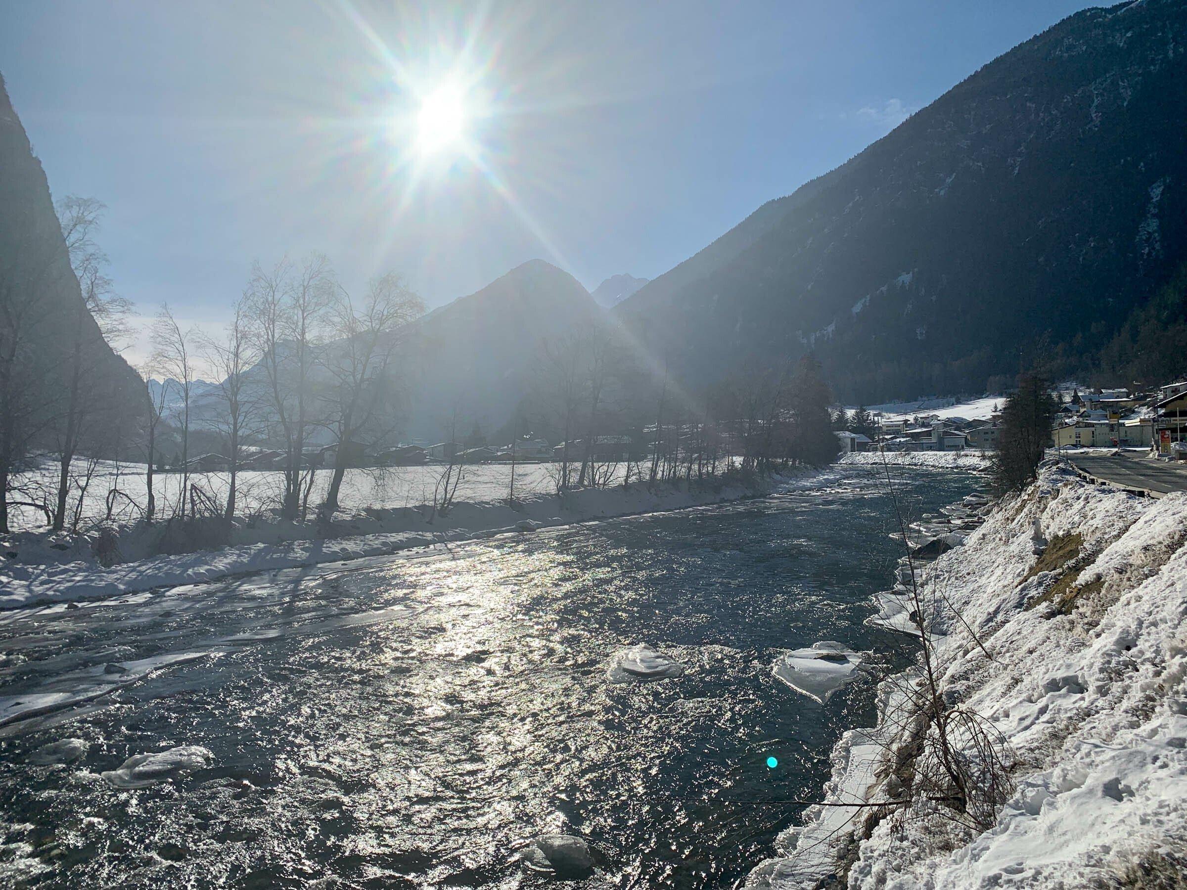Gebirgsbach in einem Tal mit Schneelandschaft und blauem Himmel