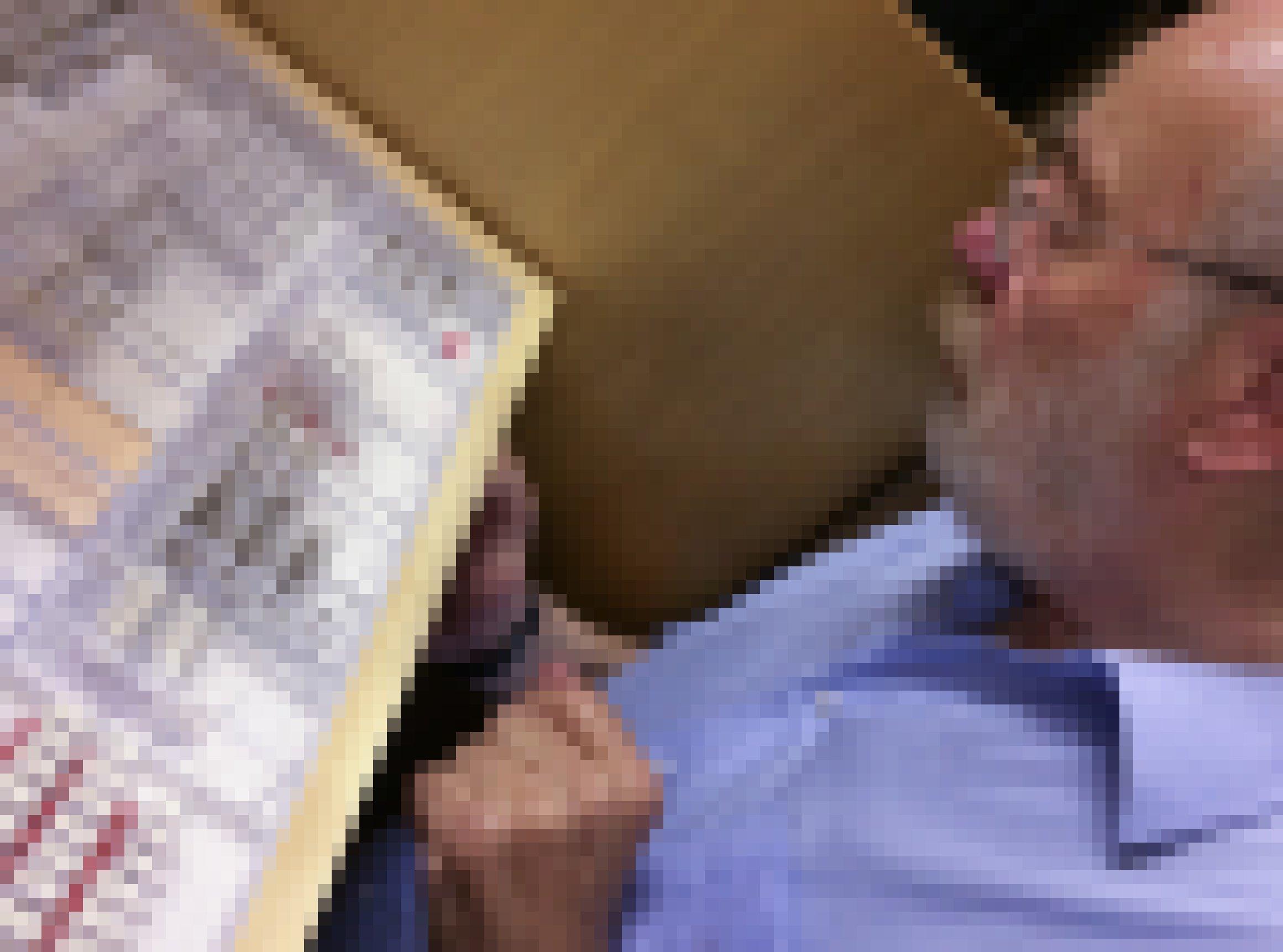 Ein Mann mit kurzen weißen Haaren und weißem Bart schaut sich einen Holzkasten mit durchsichtigem Deckel an, in dem Insekten aufgespießt sind.