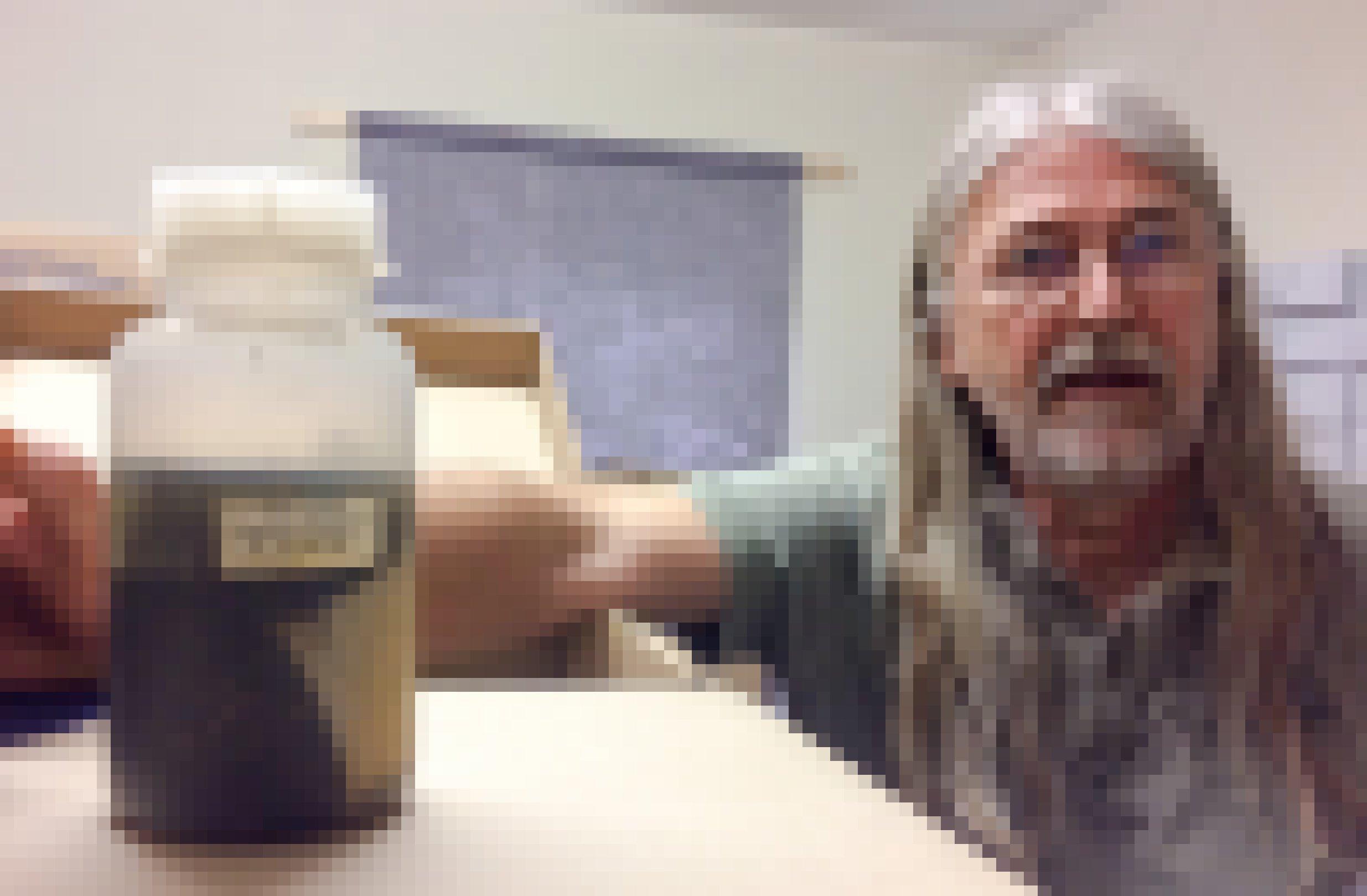 Portrait von Dr. Martin Sorg. Er ist umgeben von Pappkartons. Auf einem davon steht eine Plastikflasche, in der eine Flüssigkeit und eine große schwarze Masse von Insekten stecken.