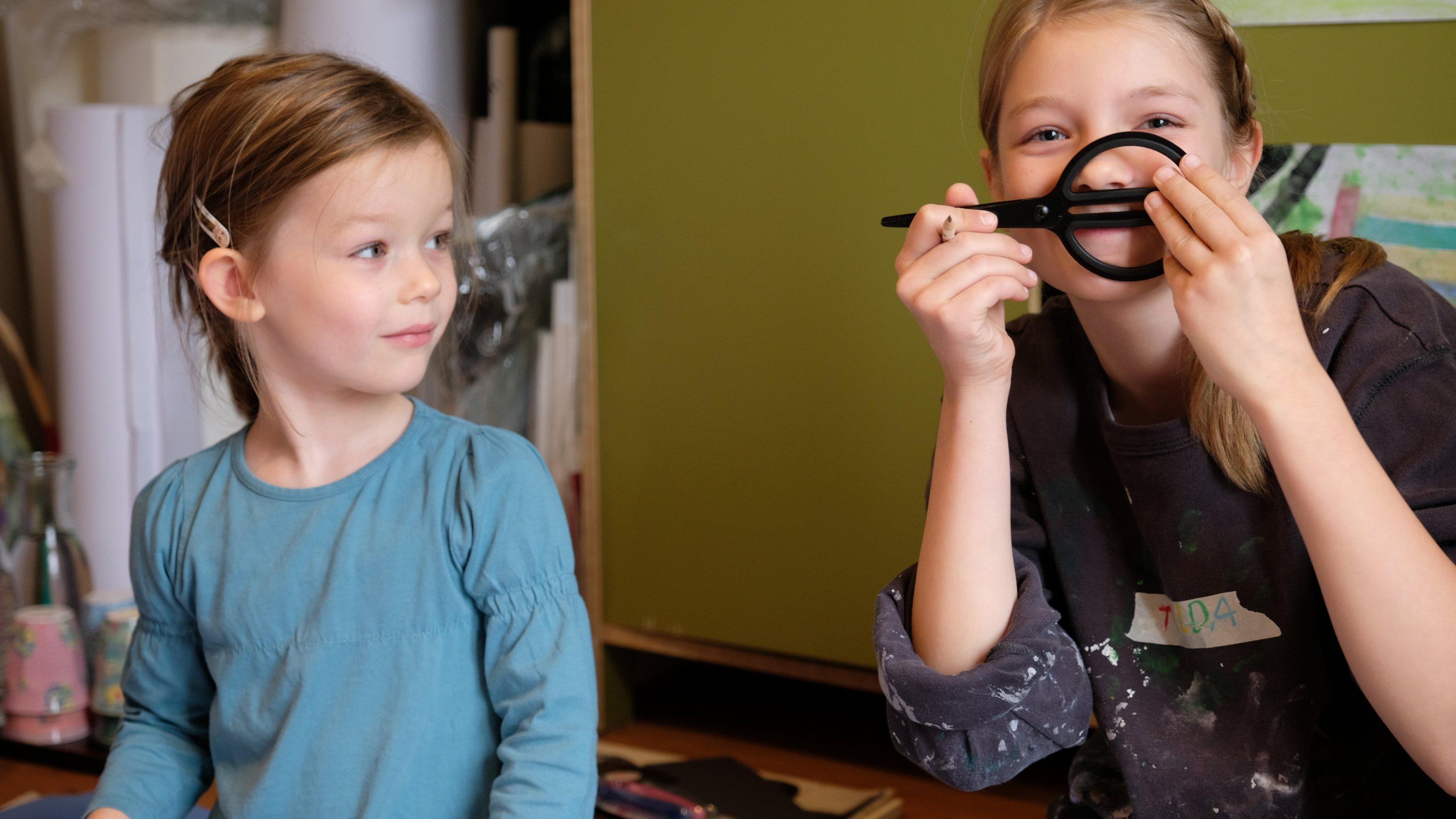 """Irma, ein fünfjähriges Mädchen, blickt auf ihre Schwester Tilda (10Jahre alt). Tilda guckt in die Kamera und macht Quatsch. Beide tragen alte Klamotten, die man dreckig machen kann. Sie wollen nämlich mit Farbe schmieren und Kunst machen """"wie Paul Klee"""". Im Hintergrund stehen große Papierrollen an der Wand."""