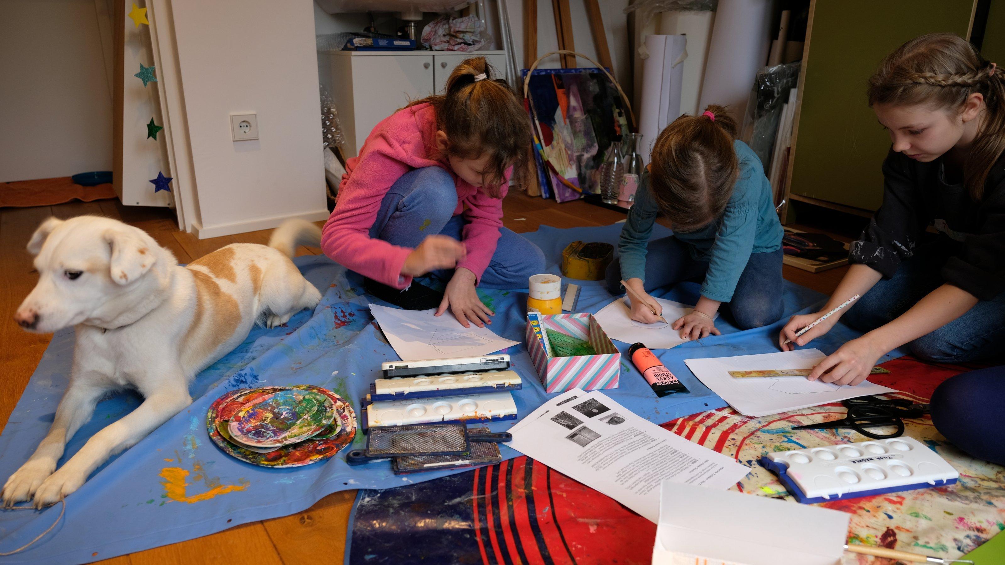 Auf einer blauen Wachstischdecke voller Farbe sitzen drei Mädchen und beginnen, ihre weißen Blätter zu gestalten. Die weiß-braune Hündin guckt zur Seite.