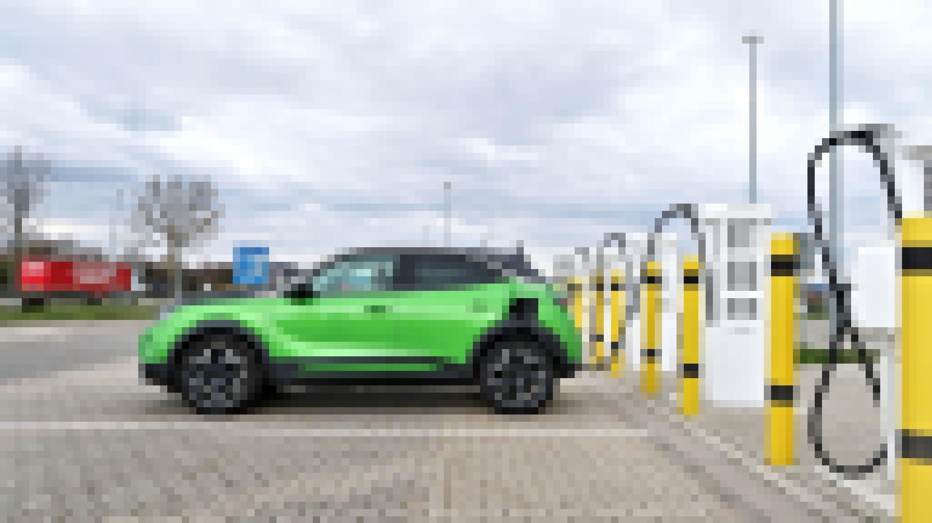 Ein grüner Opel Mokka-E lädt an einer Schnellladestation an der Autobahn auf.