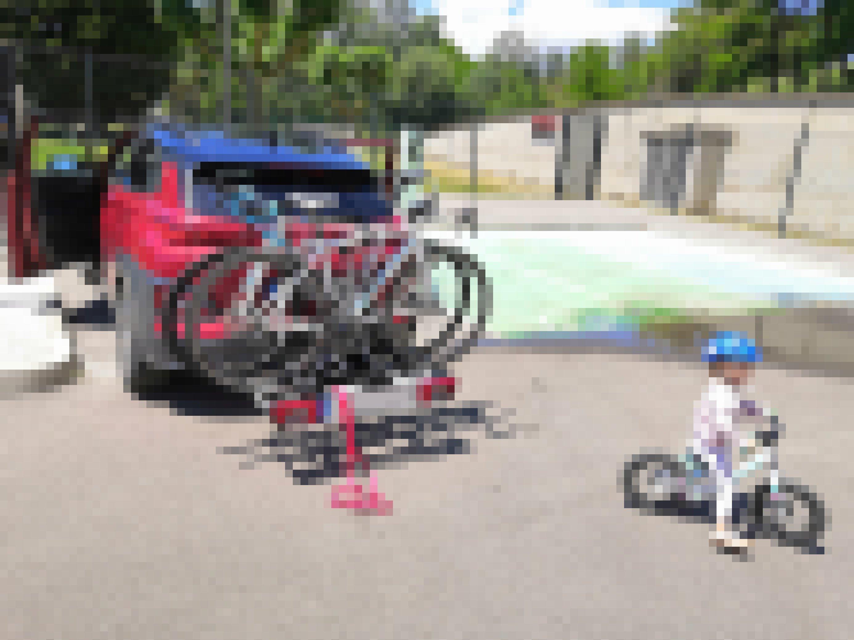 Ein Hyundai Kona tankt Strom. Im Vordergrund fährt ein kleines Mädchen mit dem Fahrrad.