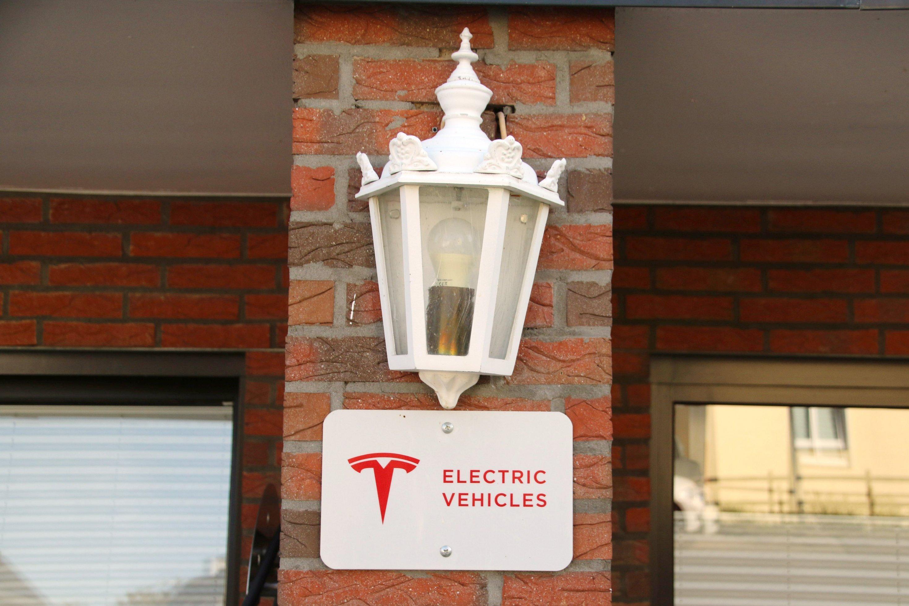 """Unter einer Lampe hängt ein Schild, auf dem """"Electric Vehicles"""" steht"""