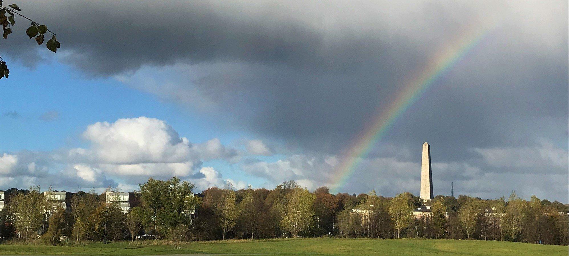 Ein Regenbogen wölbt sich über einem Obelisken am Himmel