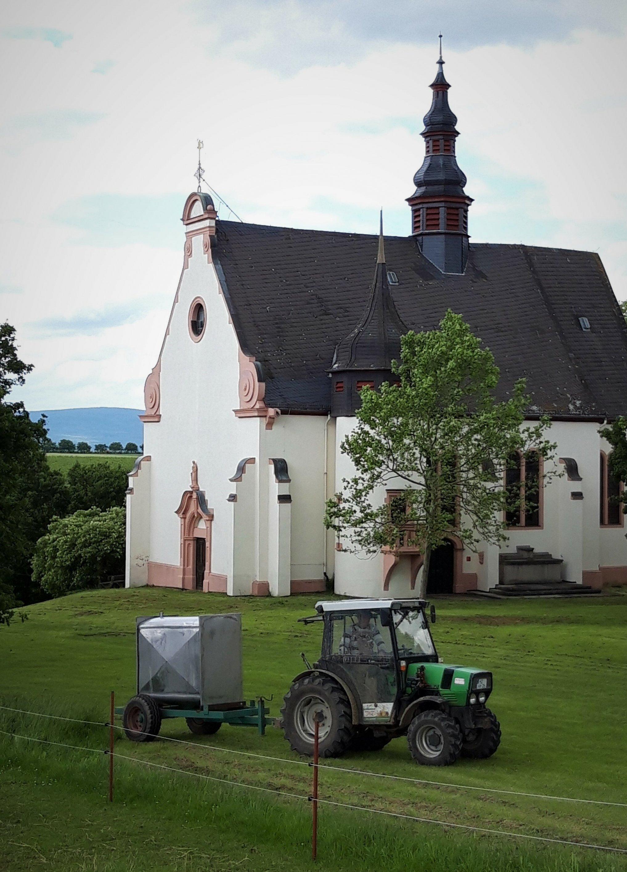 Eine kleine Barockkirche auf einer Anhöhe, umrahmt von einer Wiese, auf der ein kleiner Traktor unterwegs ist.