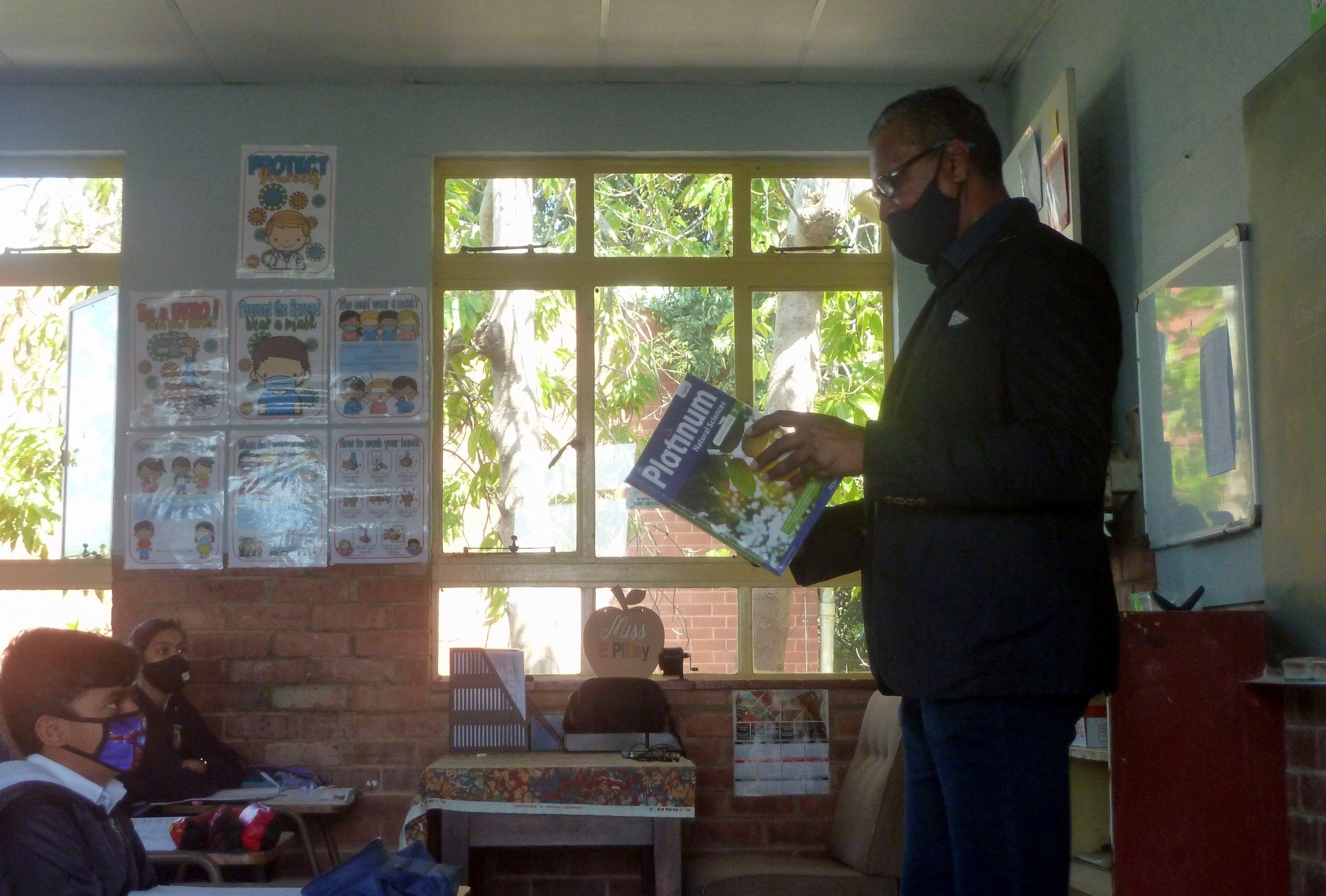 Der Lehrer steht mit einem Buch vor seiner Klasse, die Schüler schauen ihn an, an der Wand hängen Corona-Aufklärungsposter