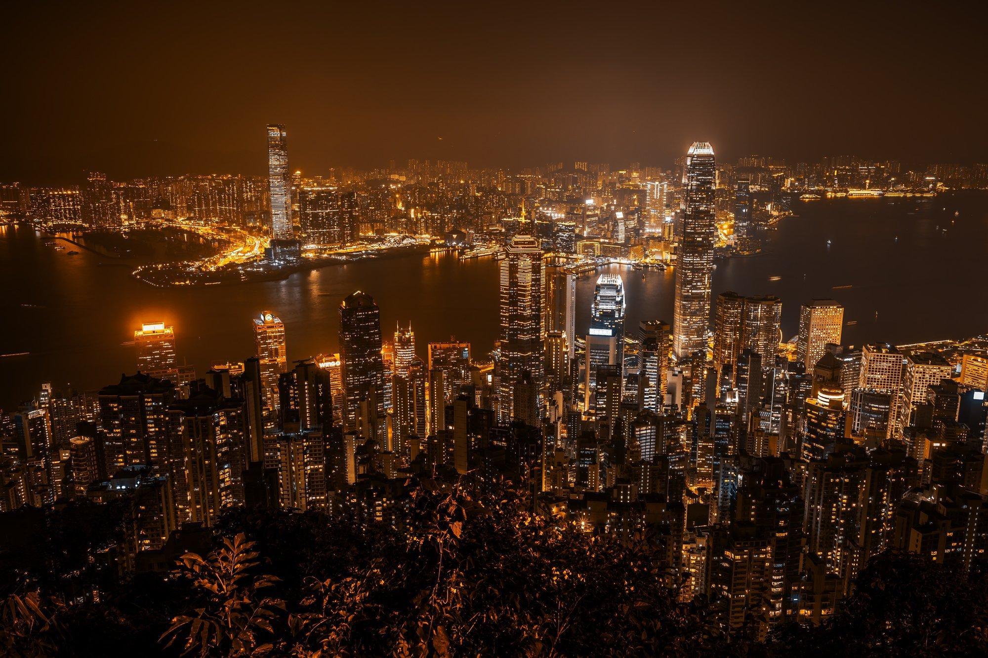 Das nachts leuchtende Hongkong mit seinen vielen Wolkenkratzern von einem Berggipfel aus gesehen.