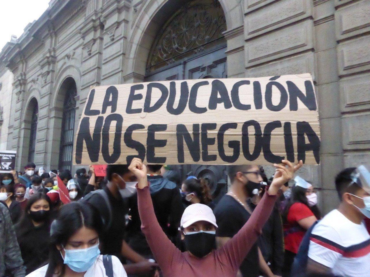 """Mehrere demonstrierende Personen stehen zusammen. Eine Frau hält einen Karton hoch, auf dem aus Spanische steht: """"Mit der Bildung macht man keine Geschäfte."""""""