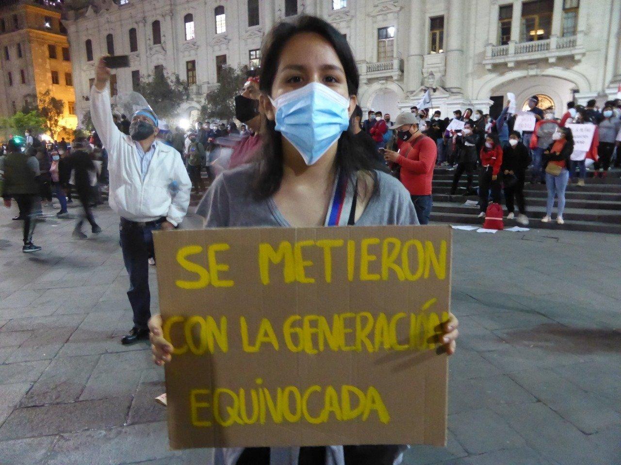 """Junge Frau mit Mundschutz trägt ein Plakat. Darauf steht auf Spanisch: """"Ihr habt Euch mit der falschen Generation angelegt."""""""