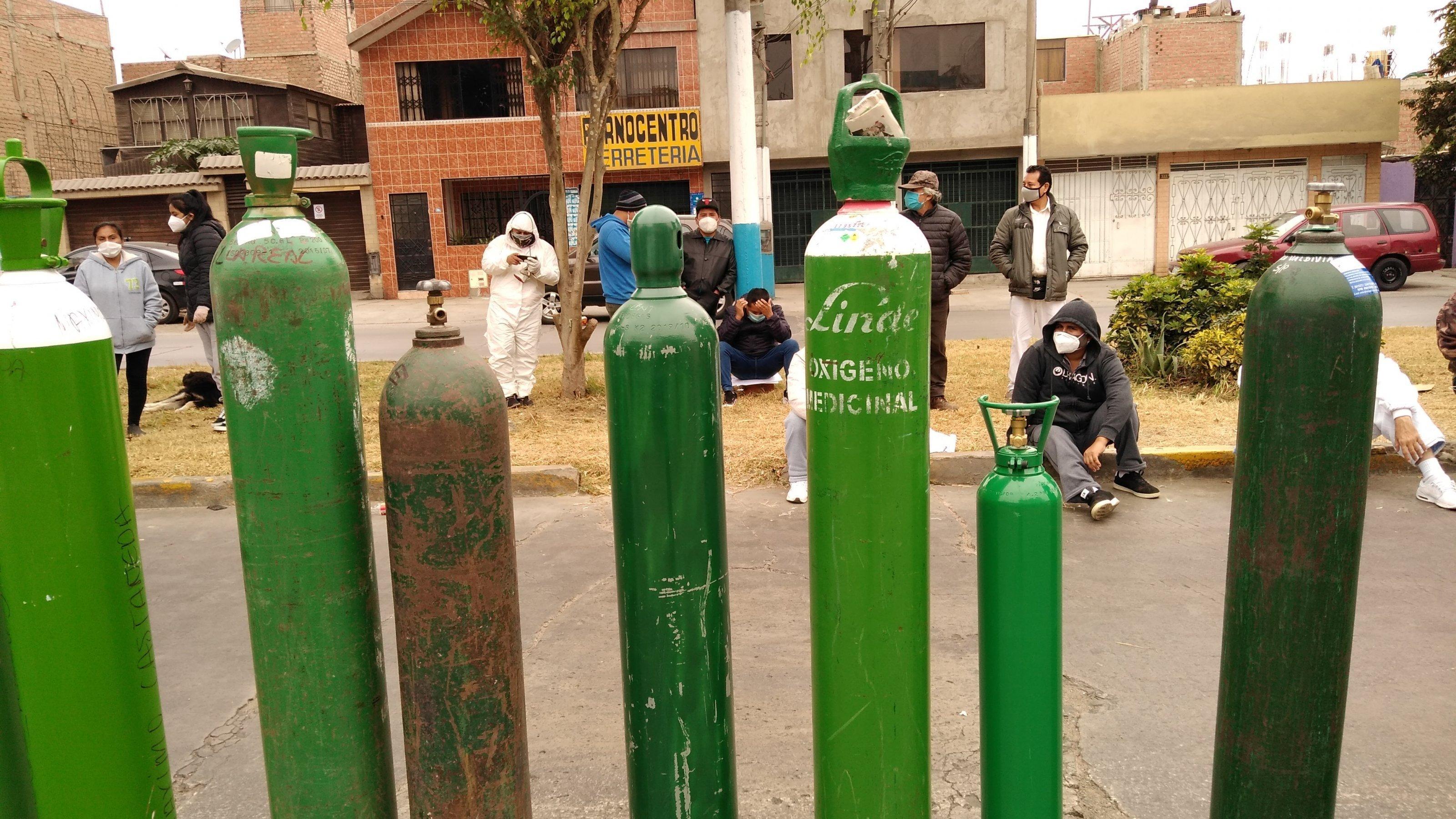 Grüne mannshohe Sauerstoff-Flaschen stehen in einer Reihe auf einer Strasse. Dahinter sieht man einige Menschen, zum Teil in Schutzkleidung.