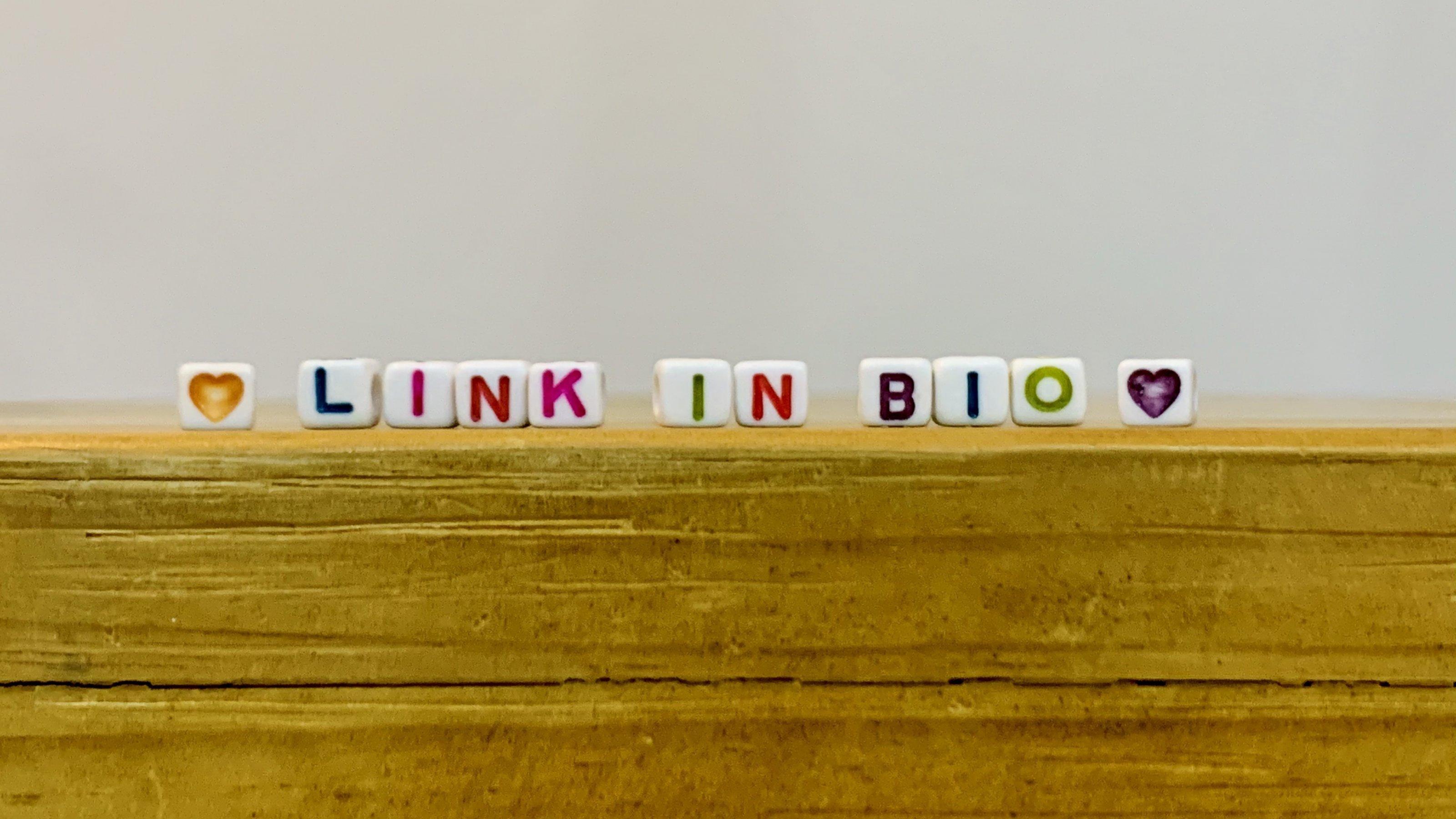 """Auf der Kante eines Holztisches sind Buchstaben eines Kinderspiels auf Würfeln angeordnet. Diese ergeben den Satz """"Link in Bio""""."""