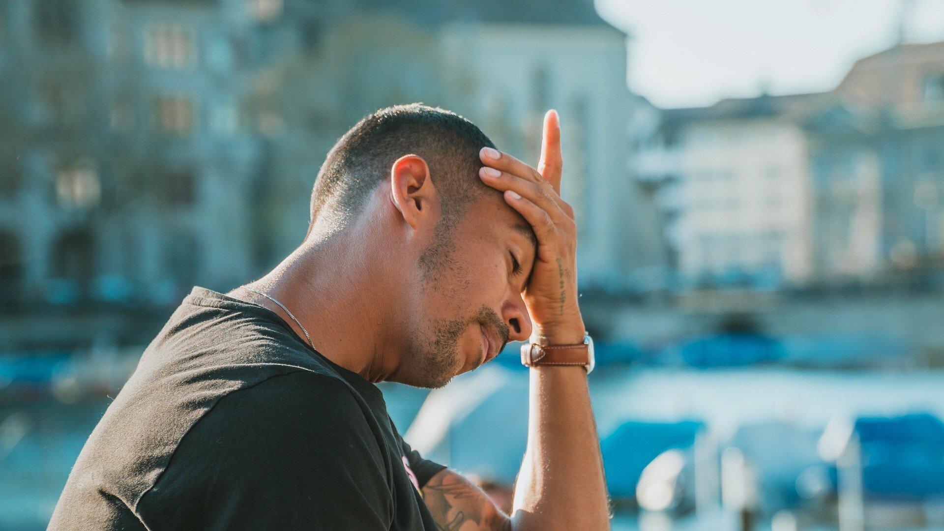 Ein junger Mann fasst sich mit der Hand an die Stirn. Er ist erschöpft.