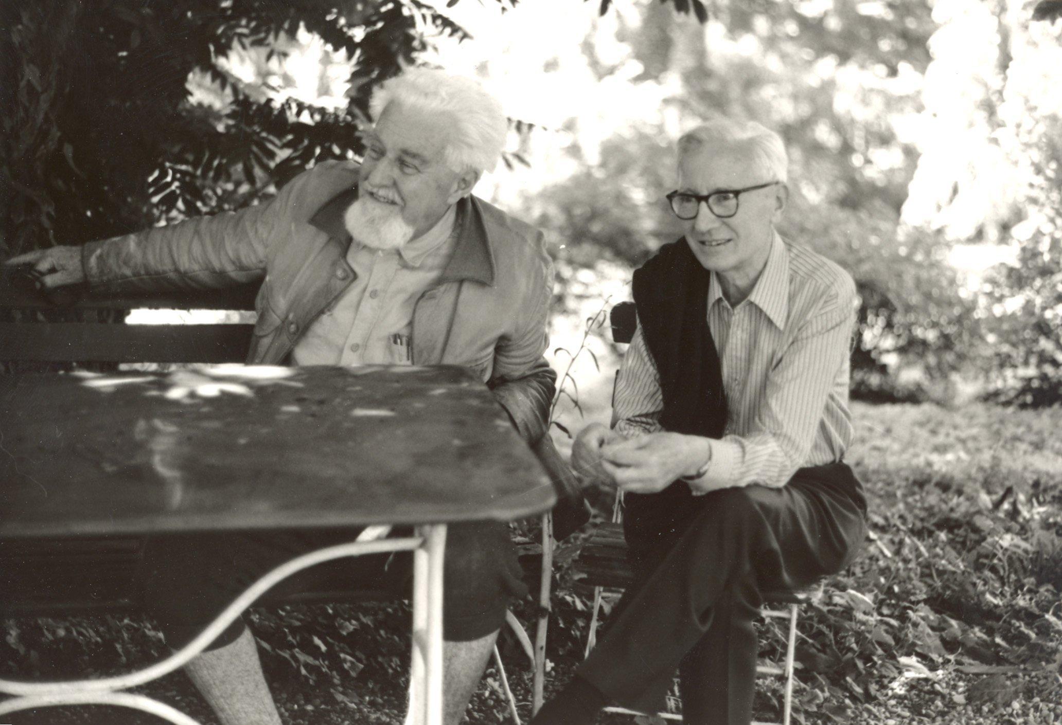 Das Bild zeigt die beiden Wissenschaftler Nikolaas Tinbergen und Konrad Lorenz in einem Garten an einem Tisch sitzend.